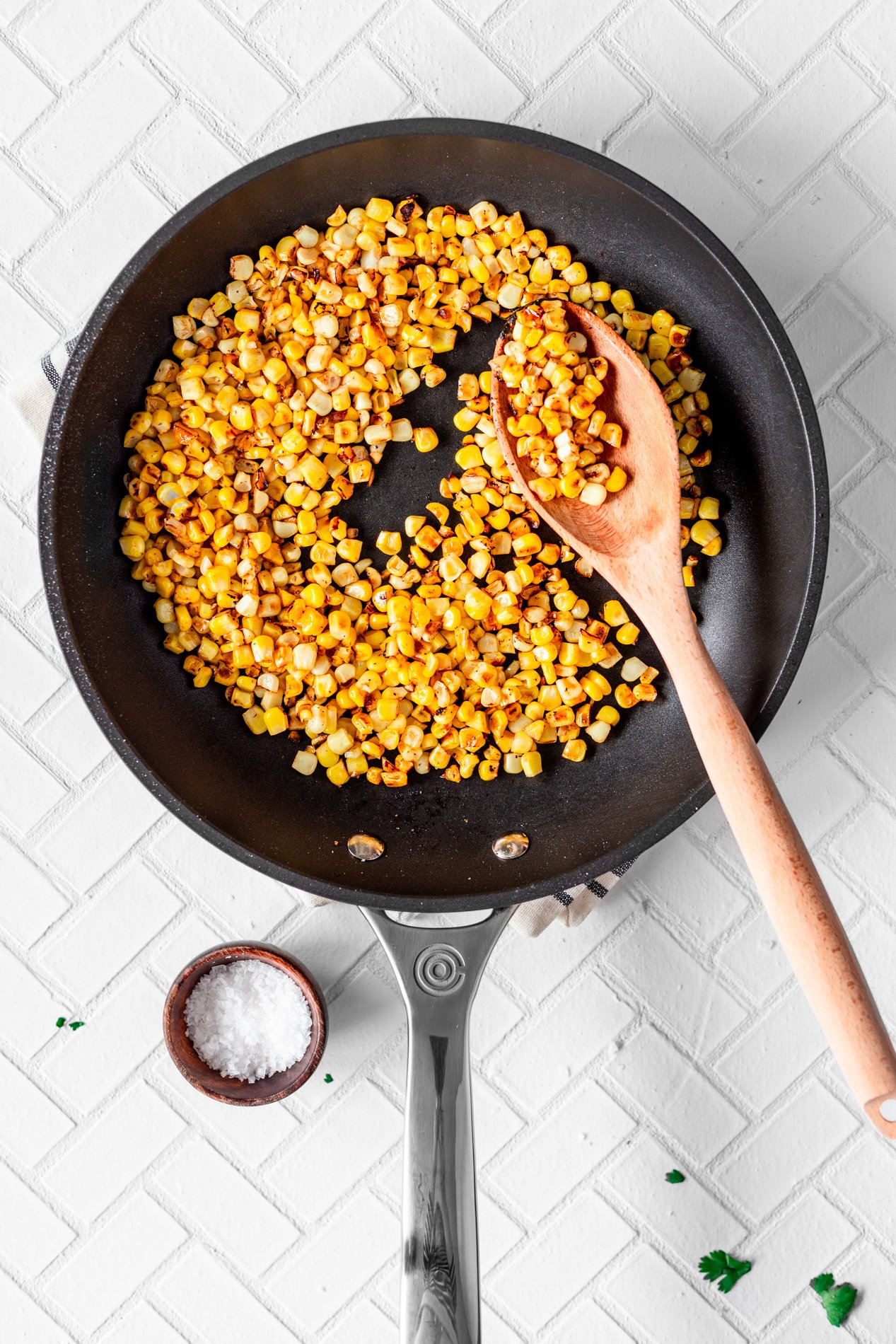 overhead view of a skillet with charred corn and a large wooden spoon with corn on it