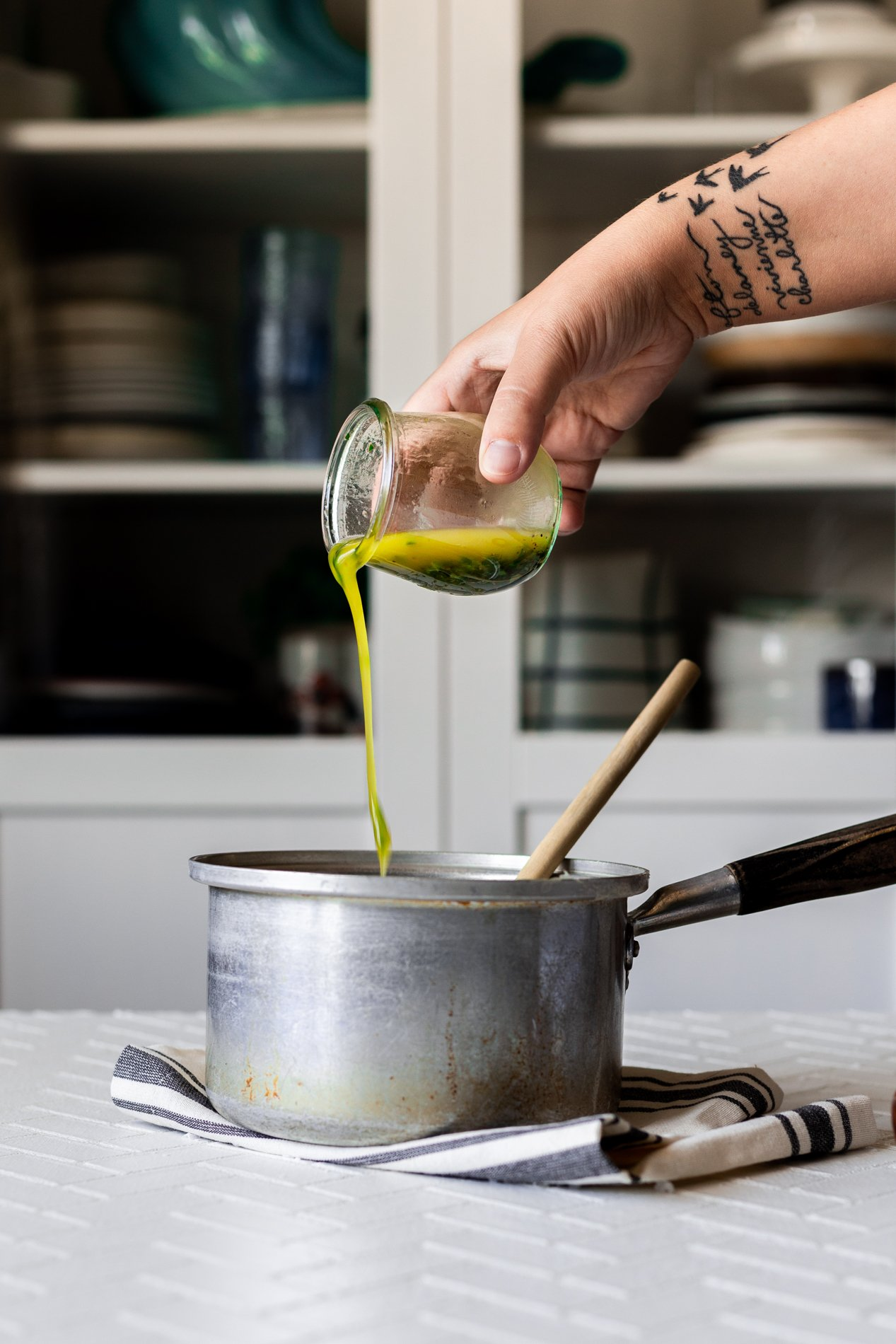 side view of a jar of lemon basil vinaigrette being poured into a pot of cooked couscous by hand