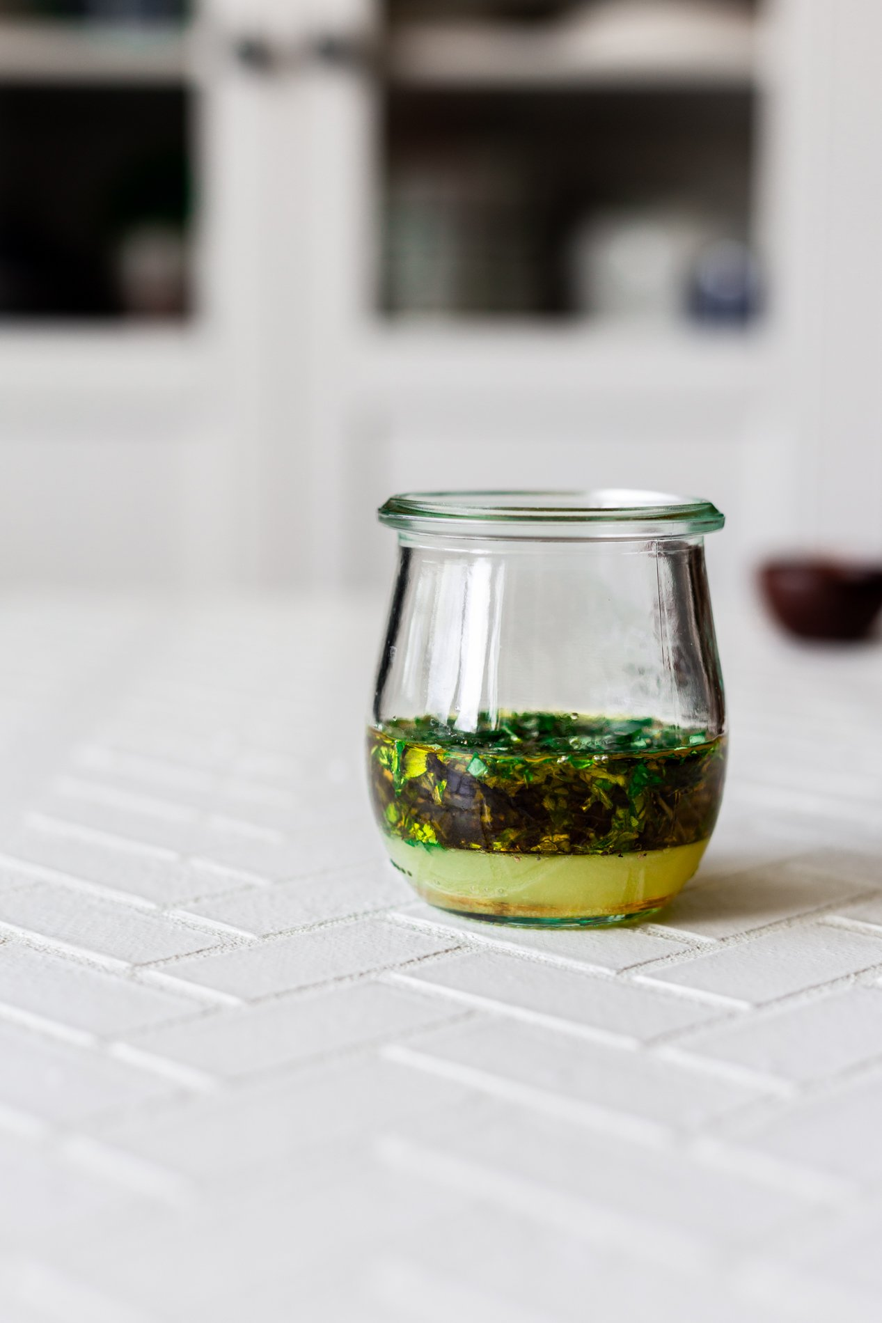 side view of a jar of lemon basil vinaigrette before being shaken