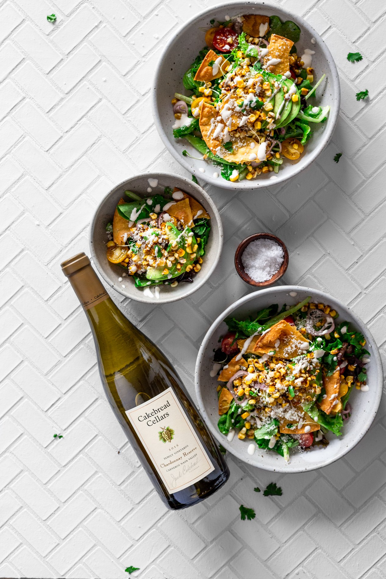 overhead view of two large and one small bowl of mexican street corn salad with a tiny bowl of sea salt and cilantro sprinkled around the bowls. a bottle of cakebread cellars wine is laying down with the label facing up
