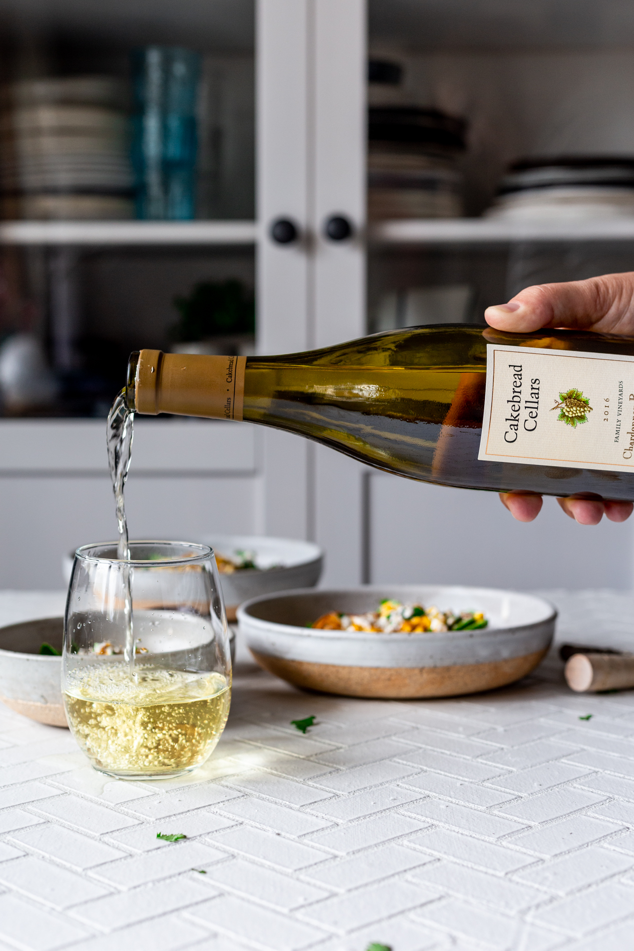 a bottle of cakebread cellars wine is being actively poured into a stemless wine glass, with three bowls of mexican street corn salad in the background