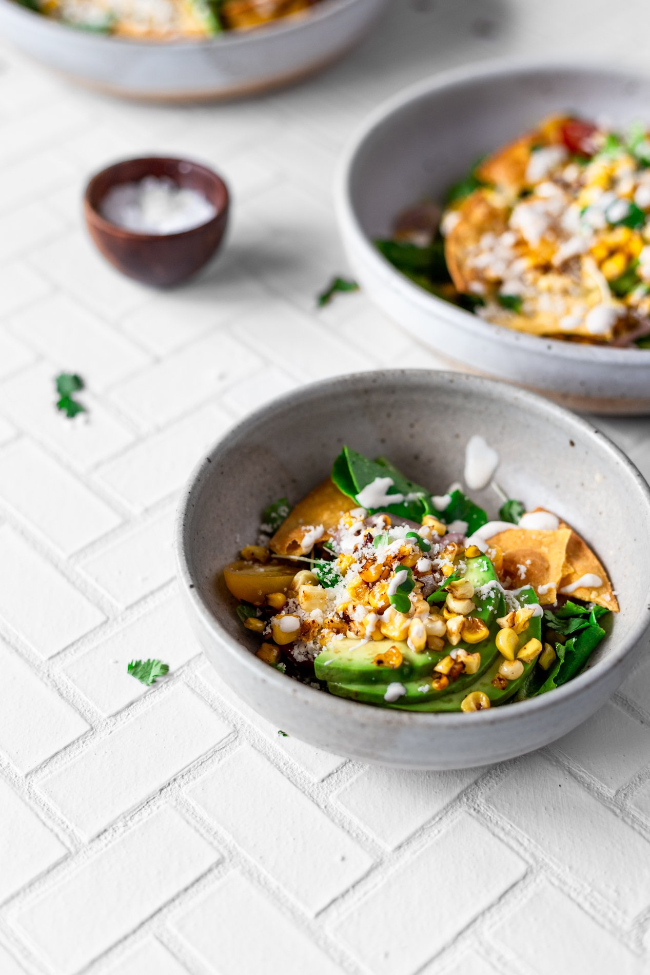 angled view of a small bowl of mexican street corn salad with two larger bowls in the background along with a tiny bowl of sea salt and scattered pieces of cilantro