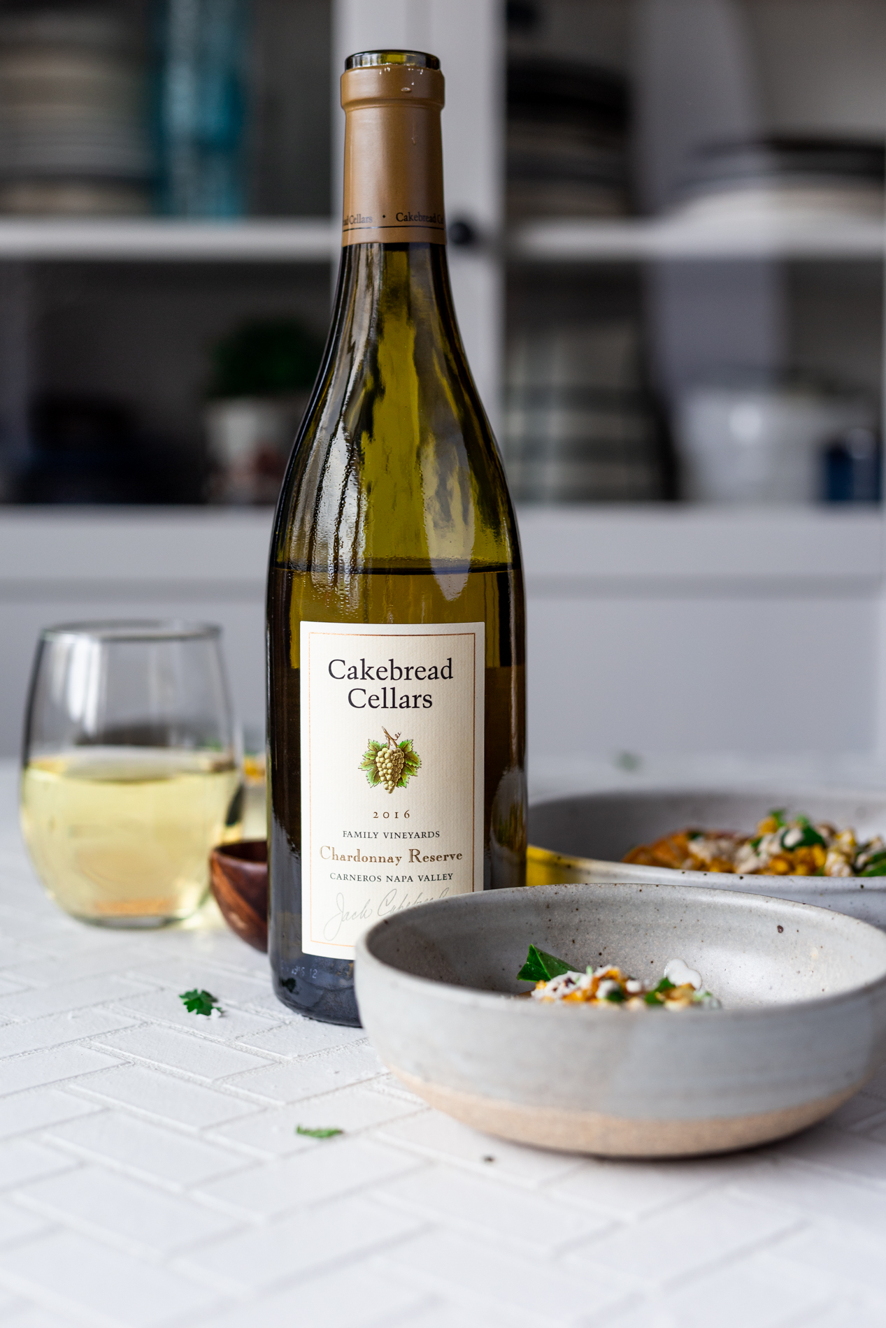 straight-ahead view of a bottle of Cakebread Cellars Chardonnay Reserve surrounded by bowls of mexican street corn salad and a glass of wine