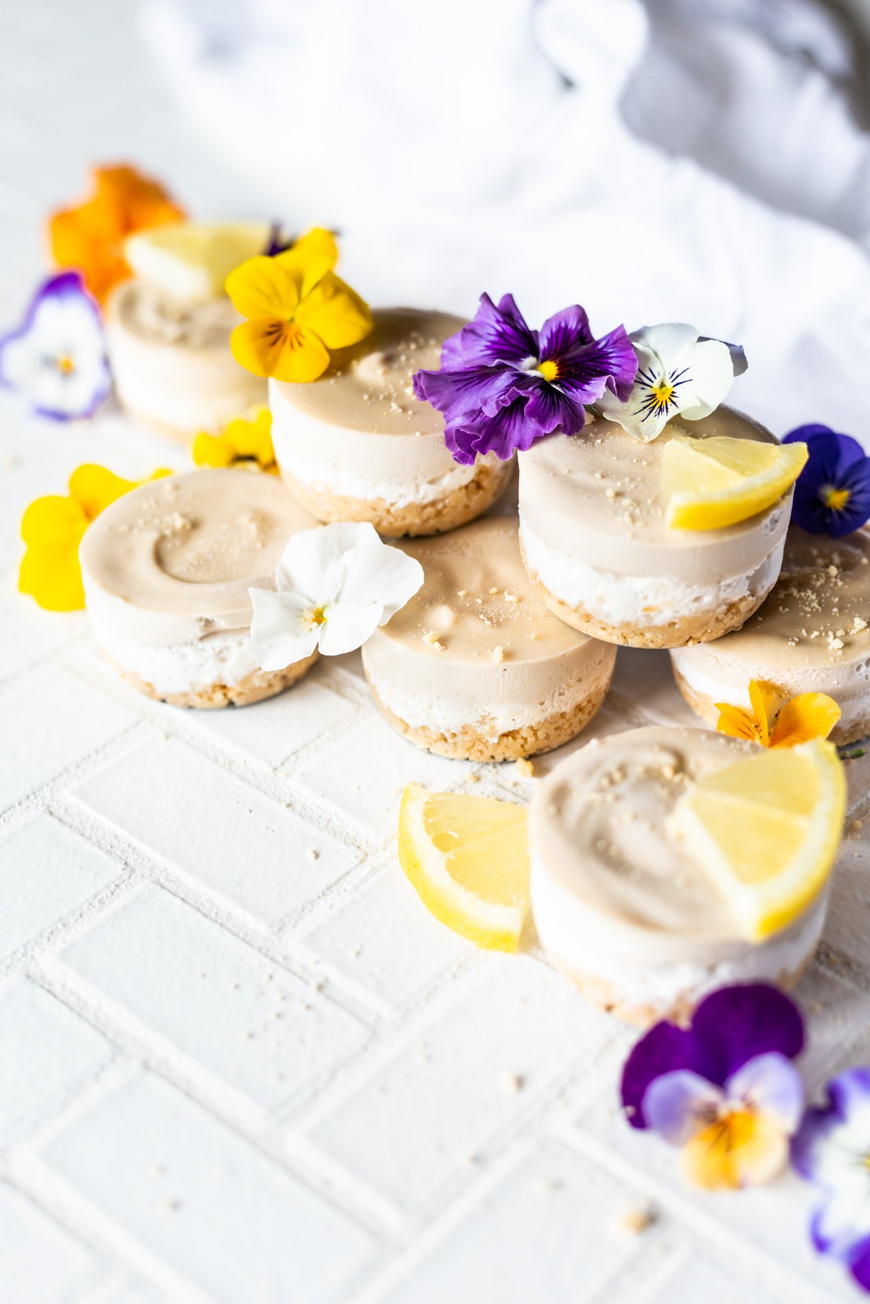 angled view of seven mini lemon vegan cheesecakes topped with lemon slices and fresh edible flowers