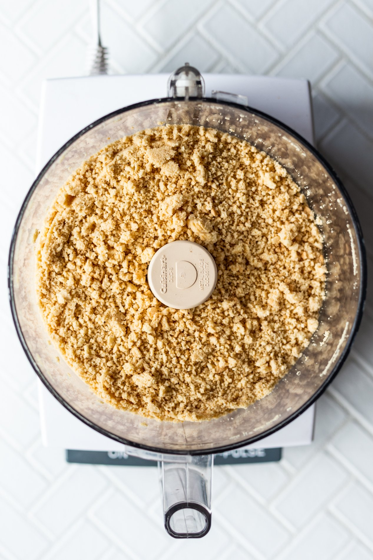 overhead view of a food processor with processed golden cookies inside
