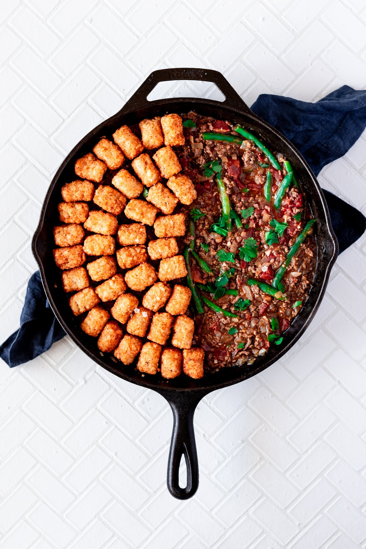 overhead view of a skillet with tater tot hotdish before the tots are baked, with the tots covering only half the skillet