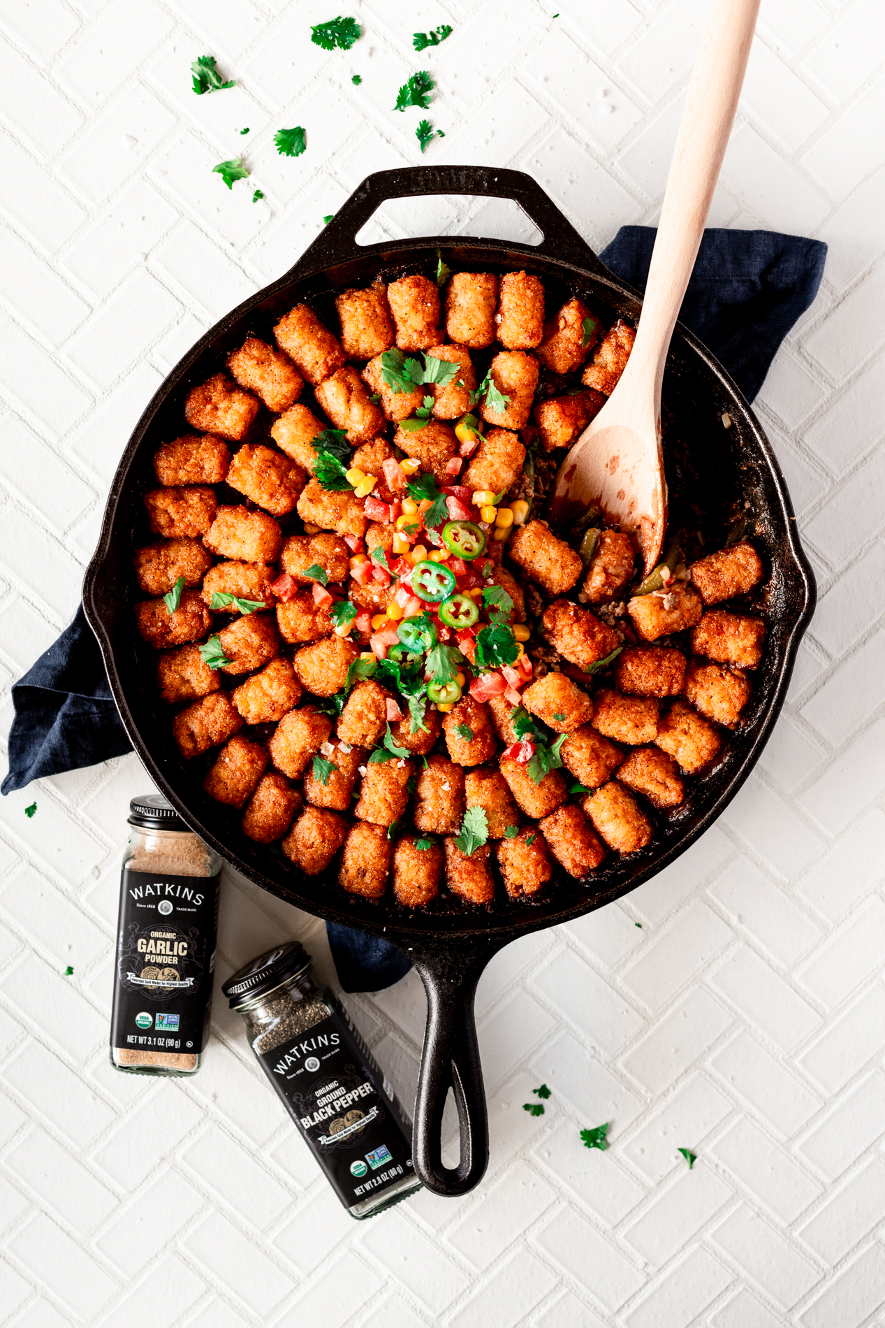 overhead view of a skillet of tater tot hotdish with a scoop removed and a wooden spoon sitting inside the skillet. two bottles of seasoning are below the skillet