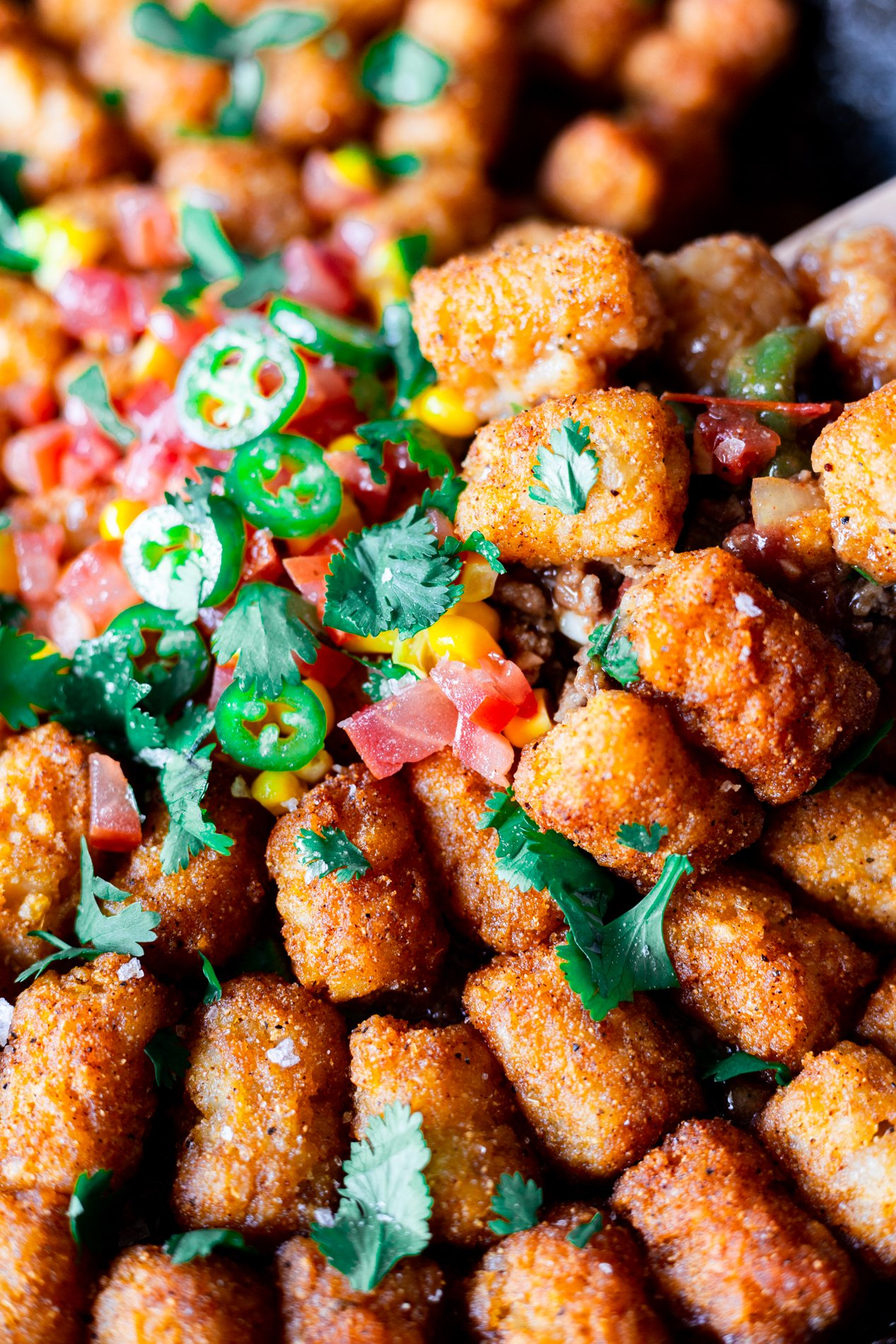 close up view of tater tot hotdish being scooped from a skillet