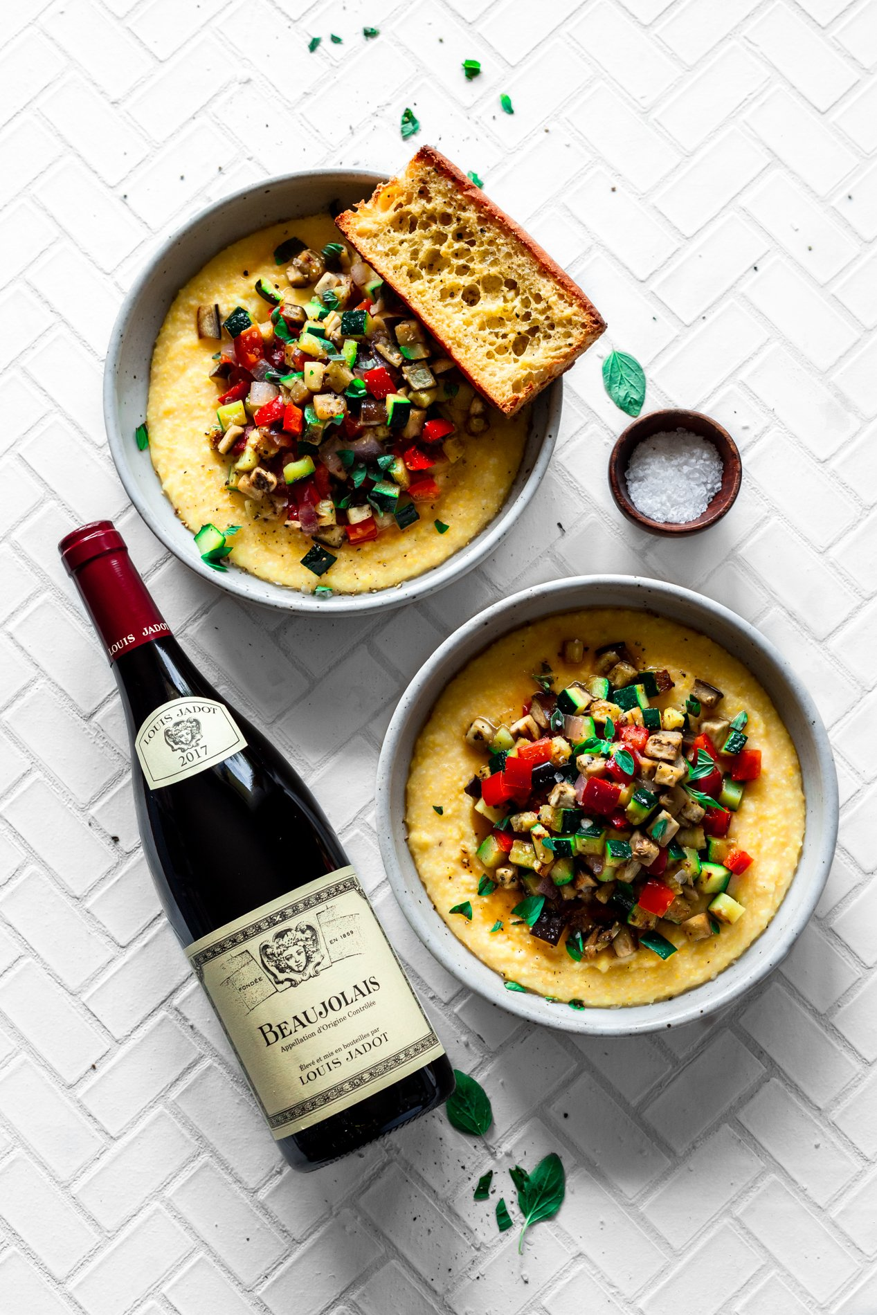 overhead view of two bowls of easy ratatouille recipe with creamy polenta, and a bottle of wine on its side