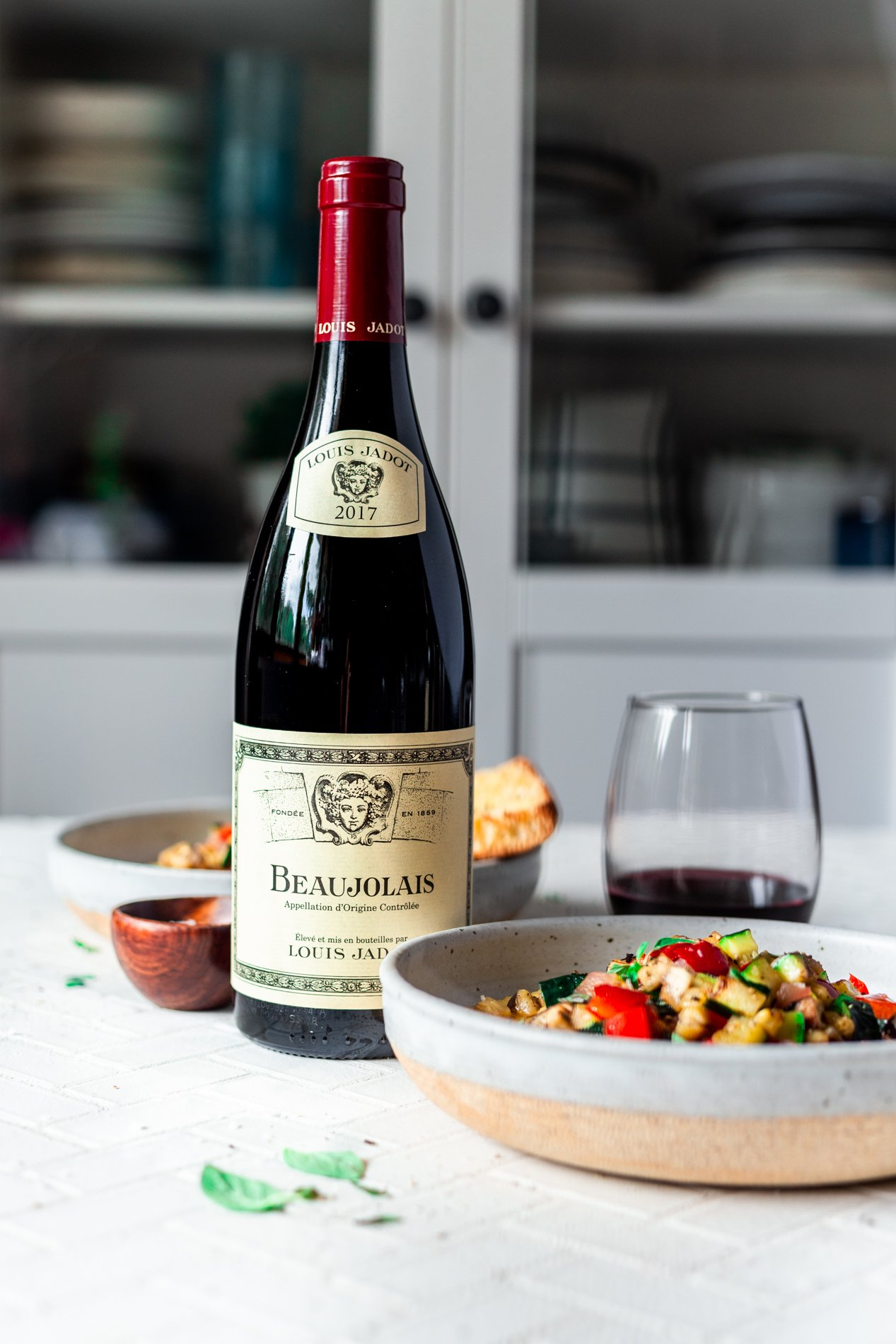 view of a bottle of louis jadot beaujolais and two bowls of easy ratatouille recipe with creamy polenta