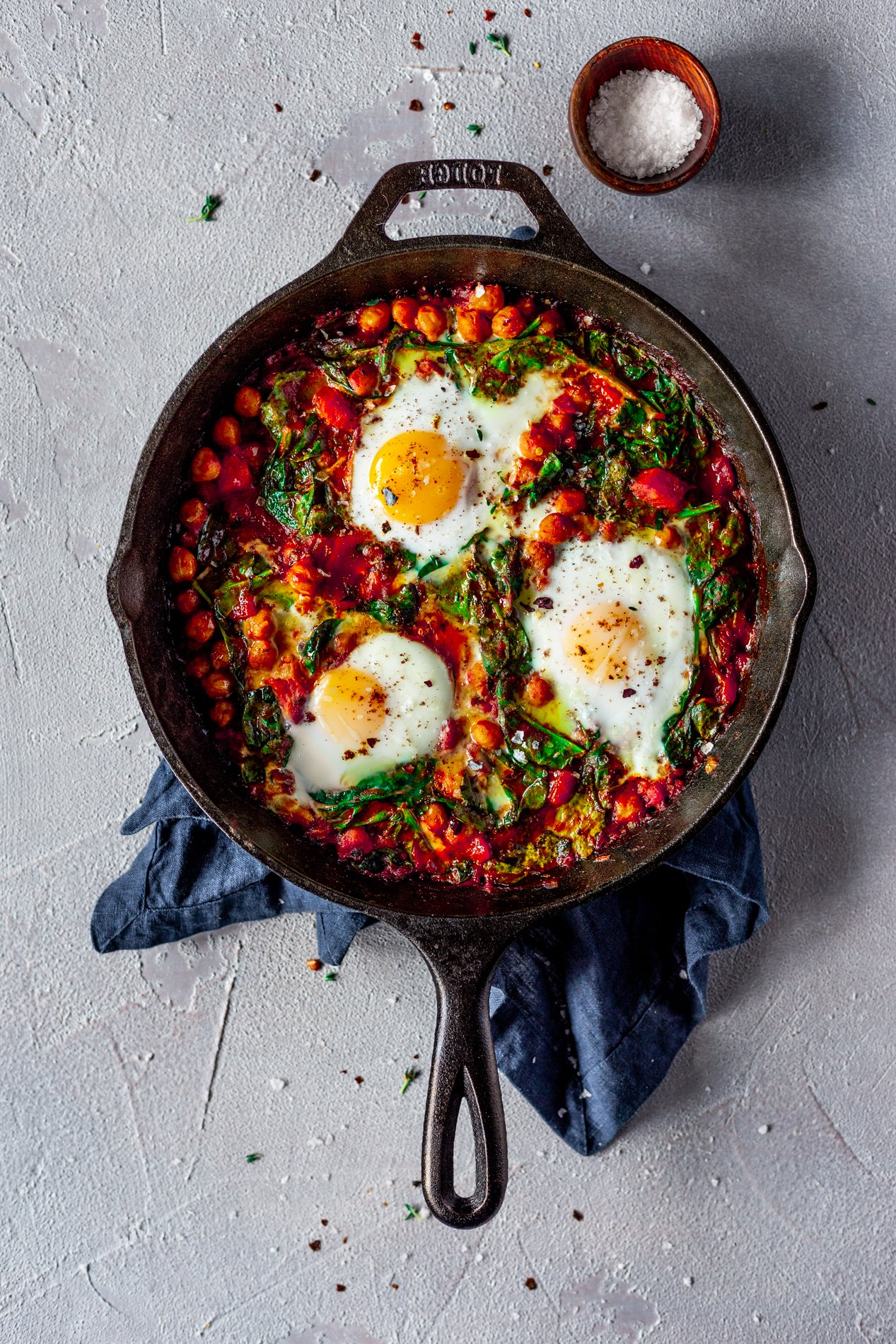 overhead view of a cast iron skillet with harissa baked eggs with chickpeas, spinach, and sumac, with a blue napkin under the skillet and a small dish of flaked salt