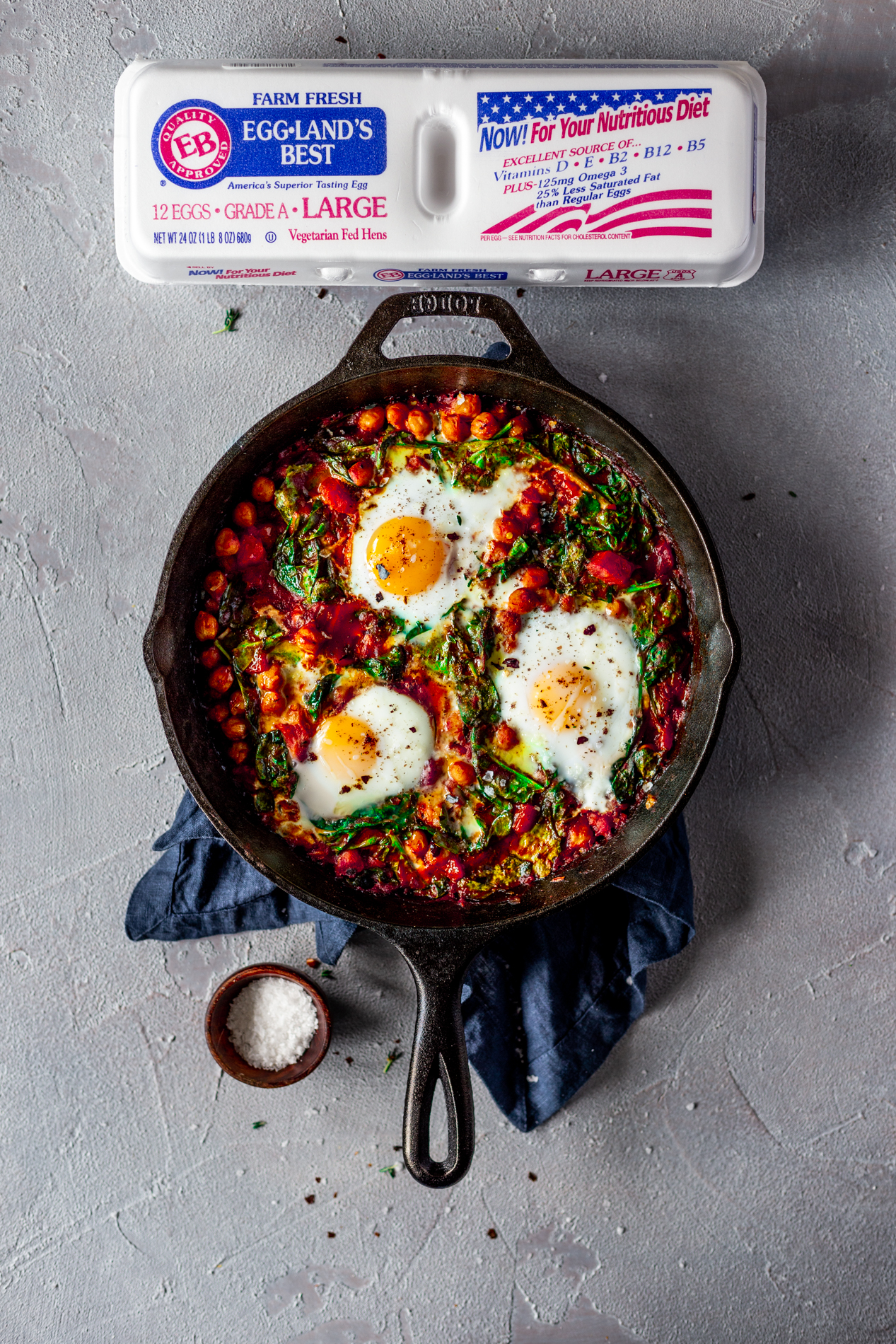 overhead view of a cast iron skillet with harissa baked eggs with chickpeas, spinach, and sumac on a blue napkin, with a carton of Eggland's Best eggs