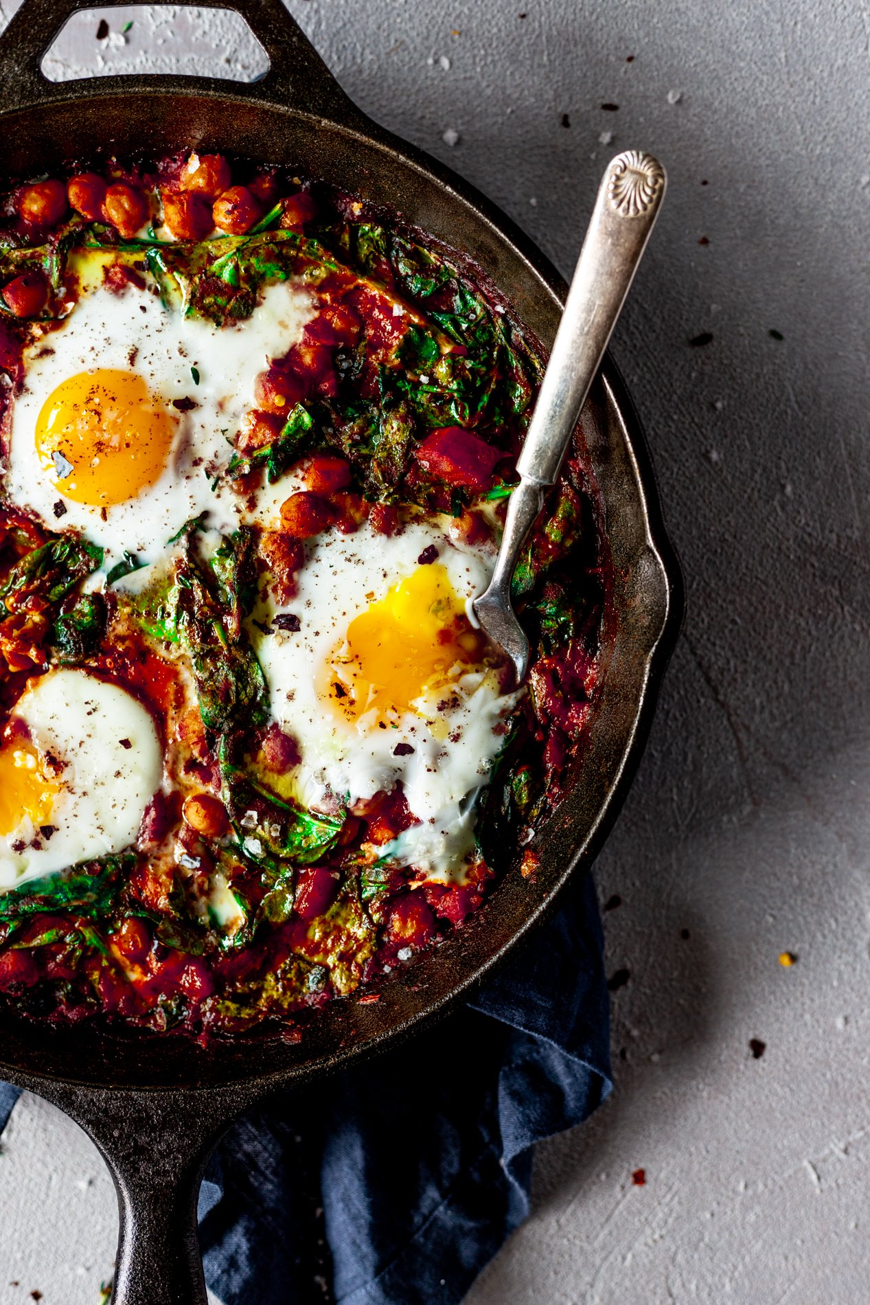 closeup overhead view of a skillet with harissa baked eggs with a fork popping one runny yolk