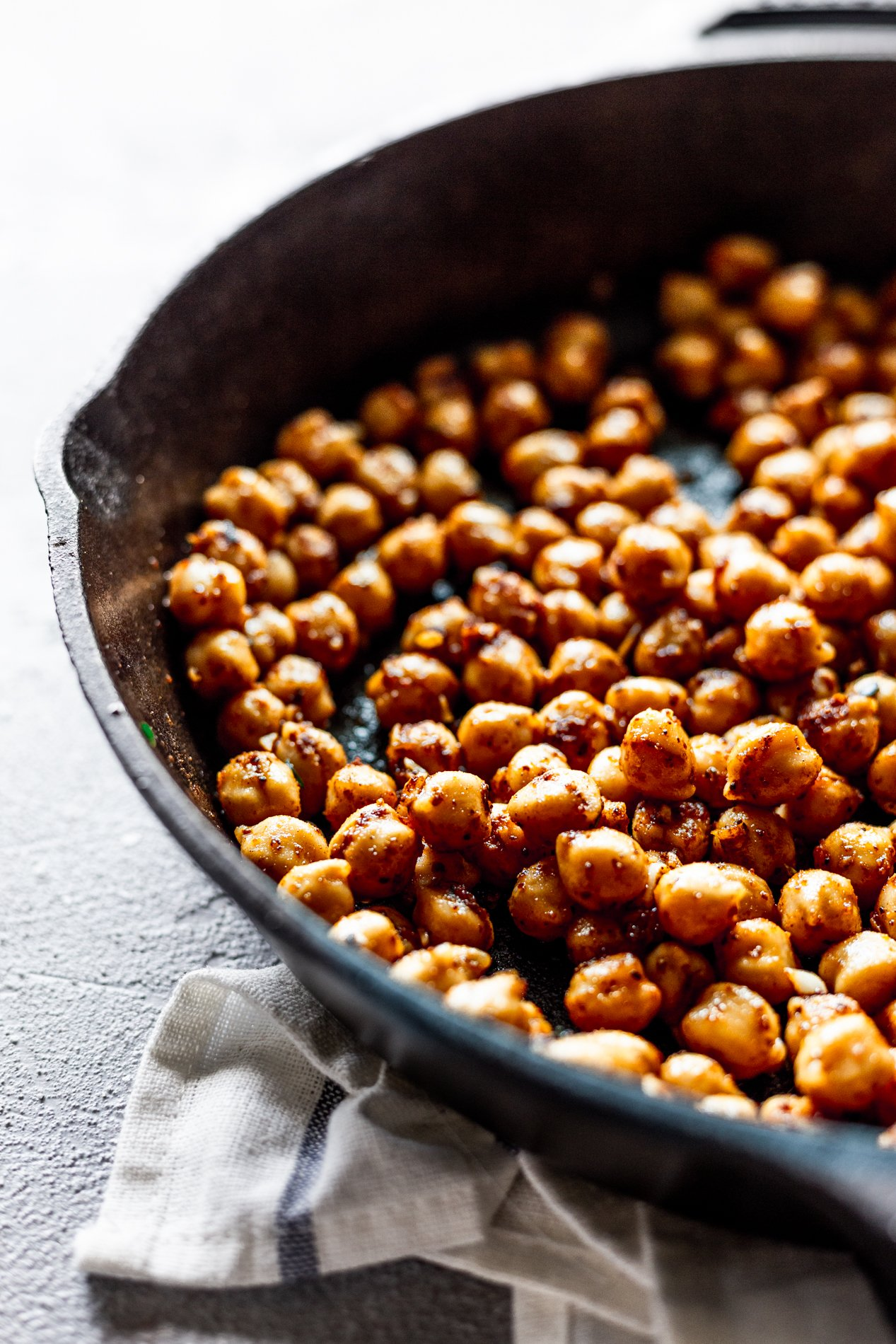 angled view of a cast iron skillet with harissa-crisped chickpeas