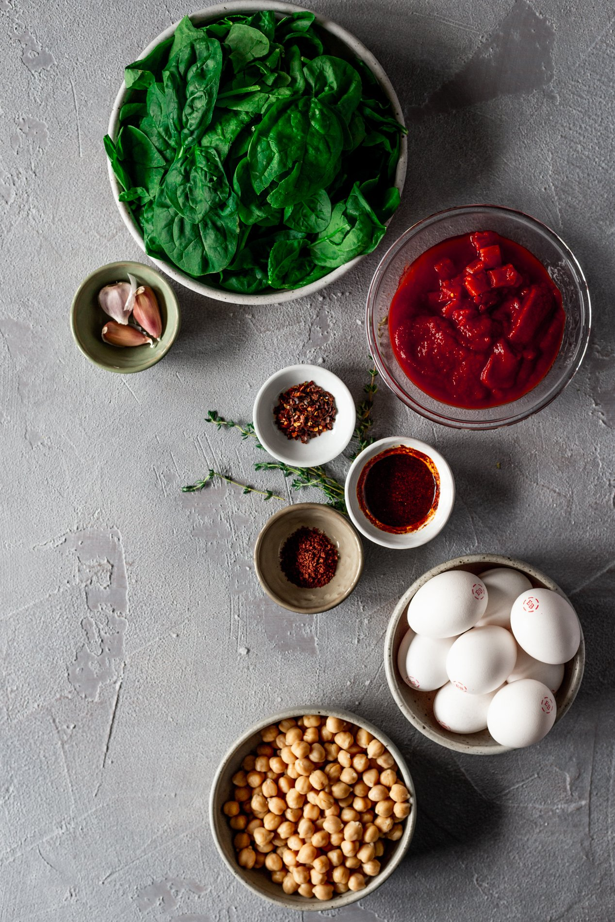 overhead view of bowls of ingredients for harissa baked eggs: spinach, tinned tomatoes, garlic cloves, red pepper flakes, harissa paste, sumac, eggs, and chickpeas