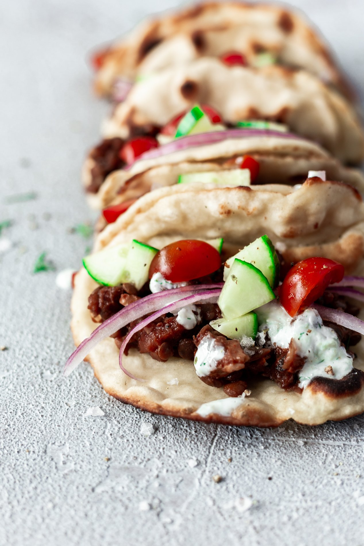 angled view of instant pot vegan gyro recipe in naan wraps all lined up in a row
