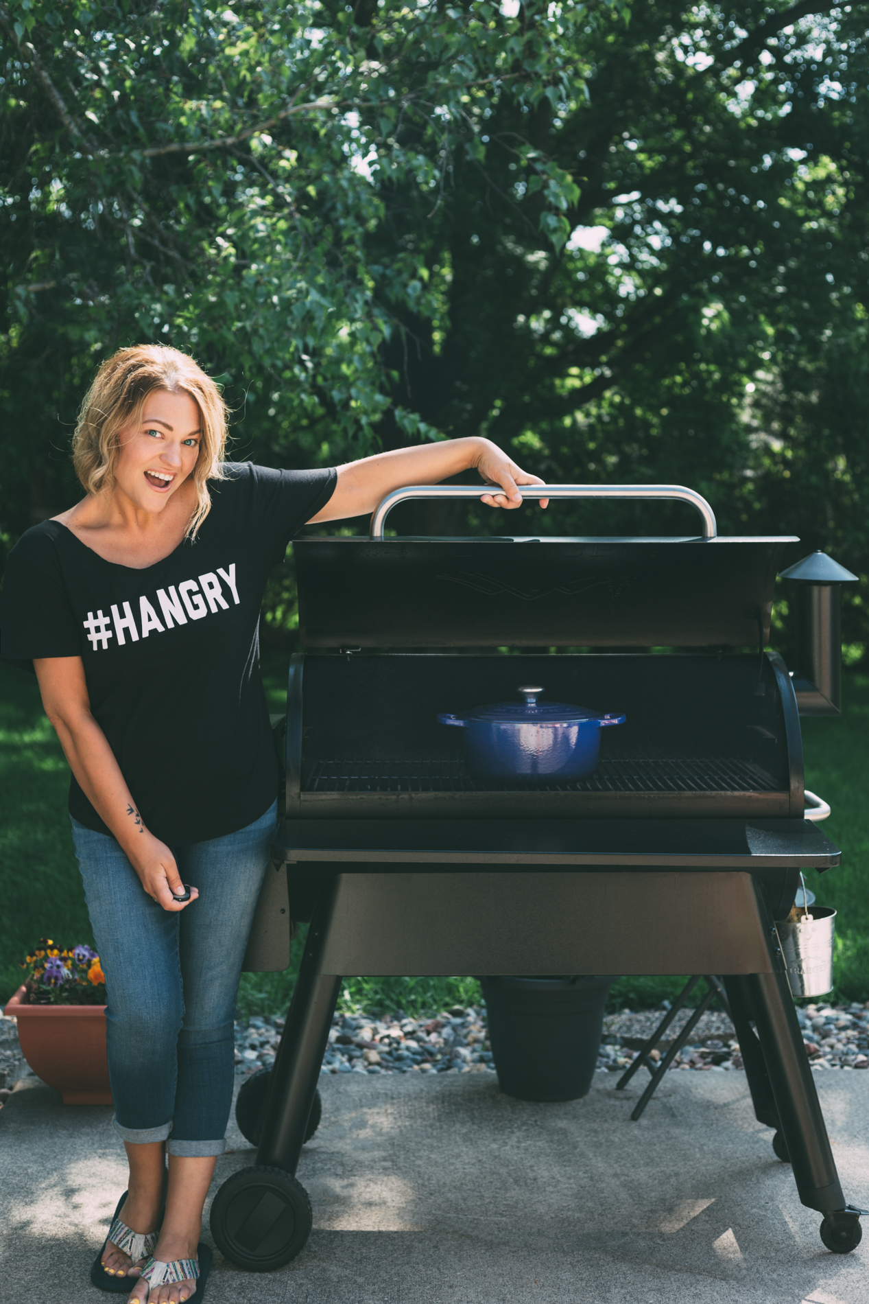 Minneapolis food blogger Karly Gomez standing next to a traeger grill with a dutch oven inside of it outside on a cement patio with a green backyard