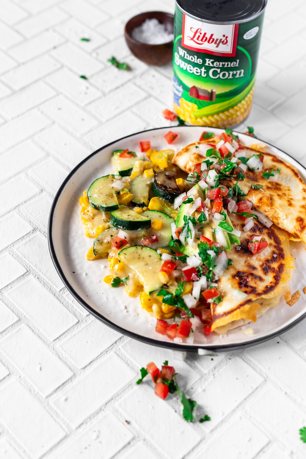 angled view of a plate of calabacitas con elote, or zucchini and corn covered with cheese, plated with quesadillas, pico de gallo, and avocado