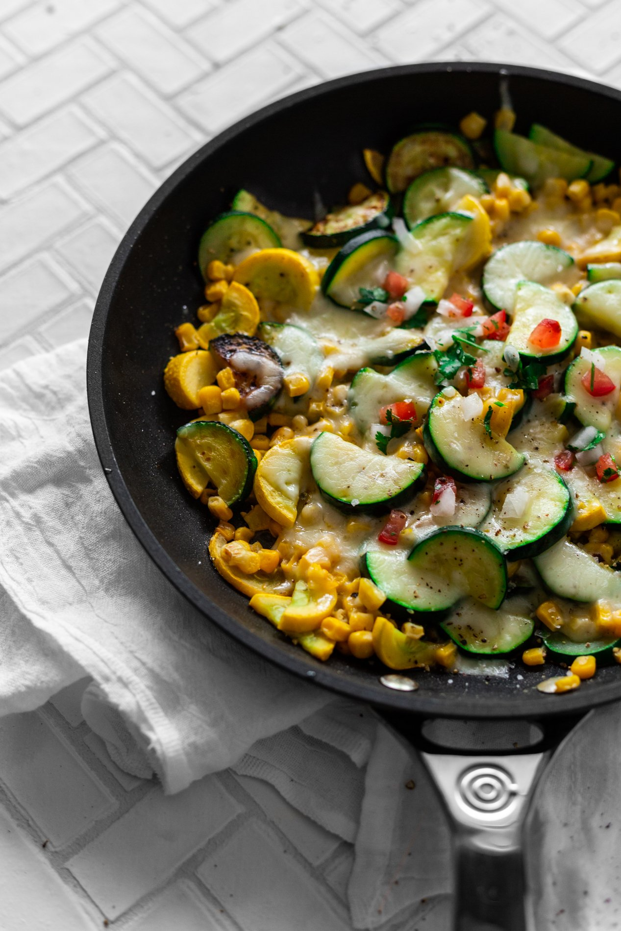 angled view of a skillet with calabacitas con elote, or zucchini with corn and cheese, sprinkled with tomatoes and cilantro