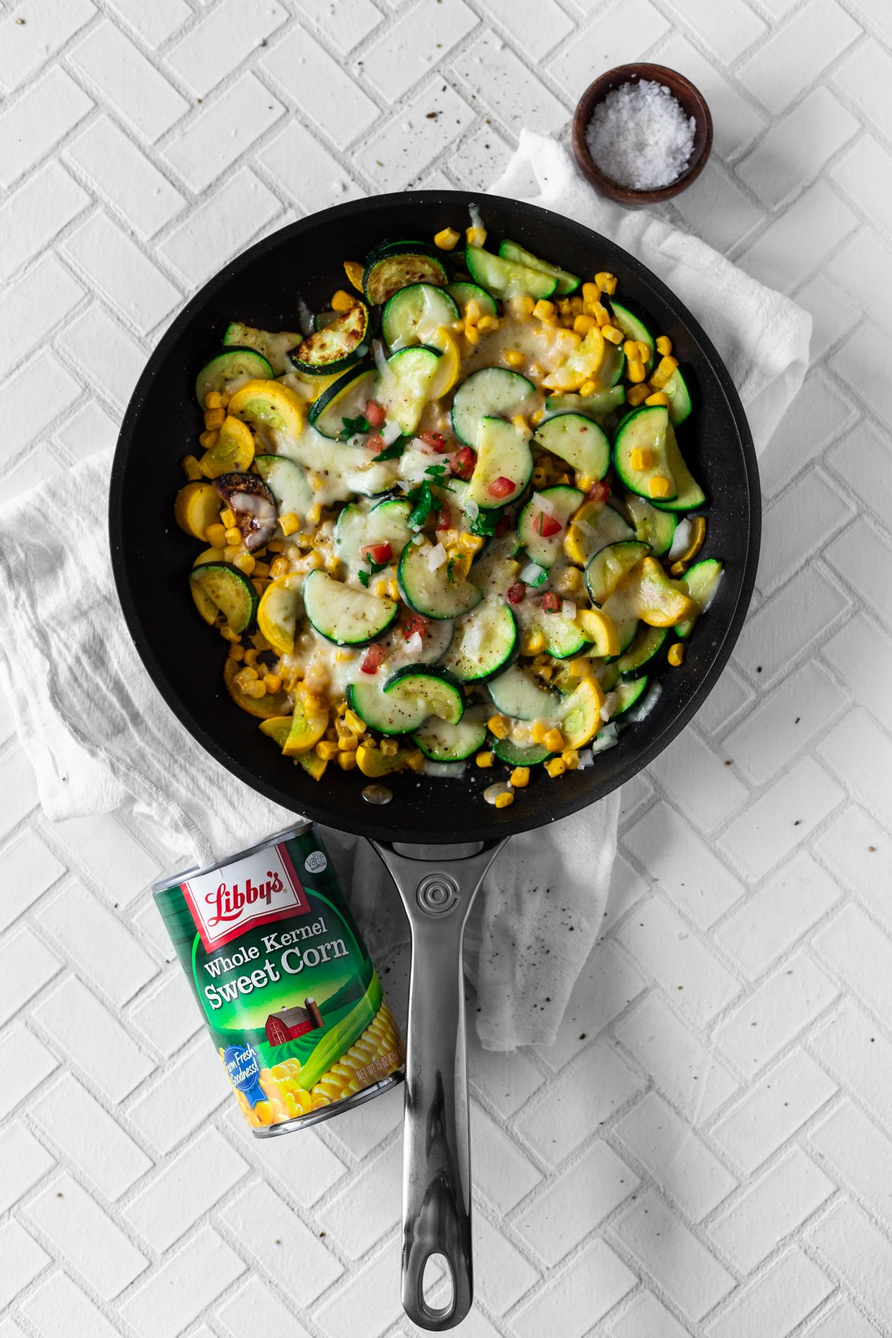 overhead view of a skillet with calabacitas con elote, or zucchini and corn, topped with cheese, with a can of corn toward the bottom of the image