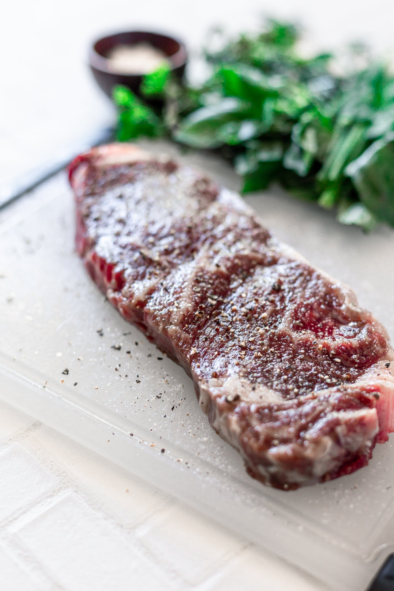 angled view of seasoned steak on cutting board and herbs in the background