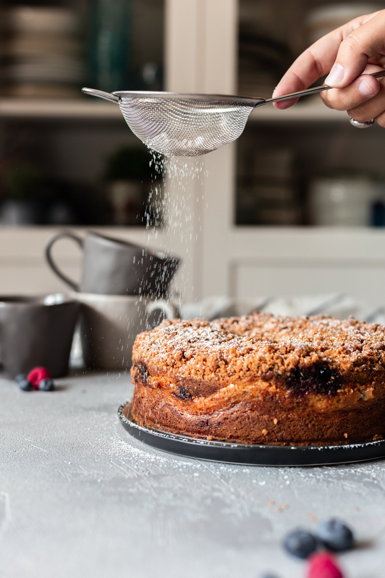 sprinkling powdered sugar on a triple berry vegan coffee cake