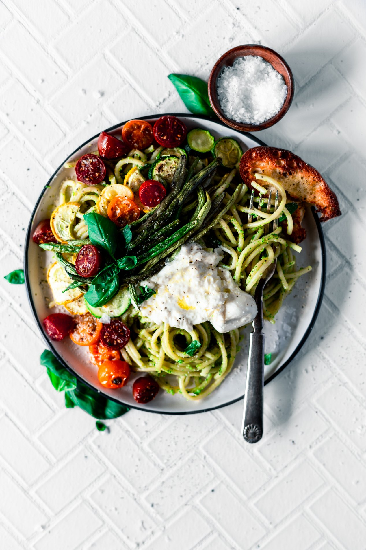 overhead view of a plate of walnut pesto pasta with roasted summer vegetables and a dollop of burrata