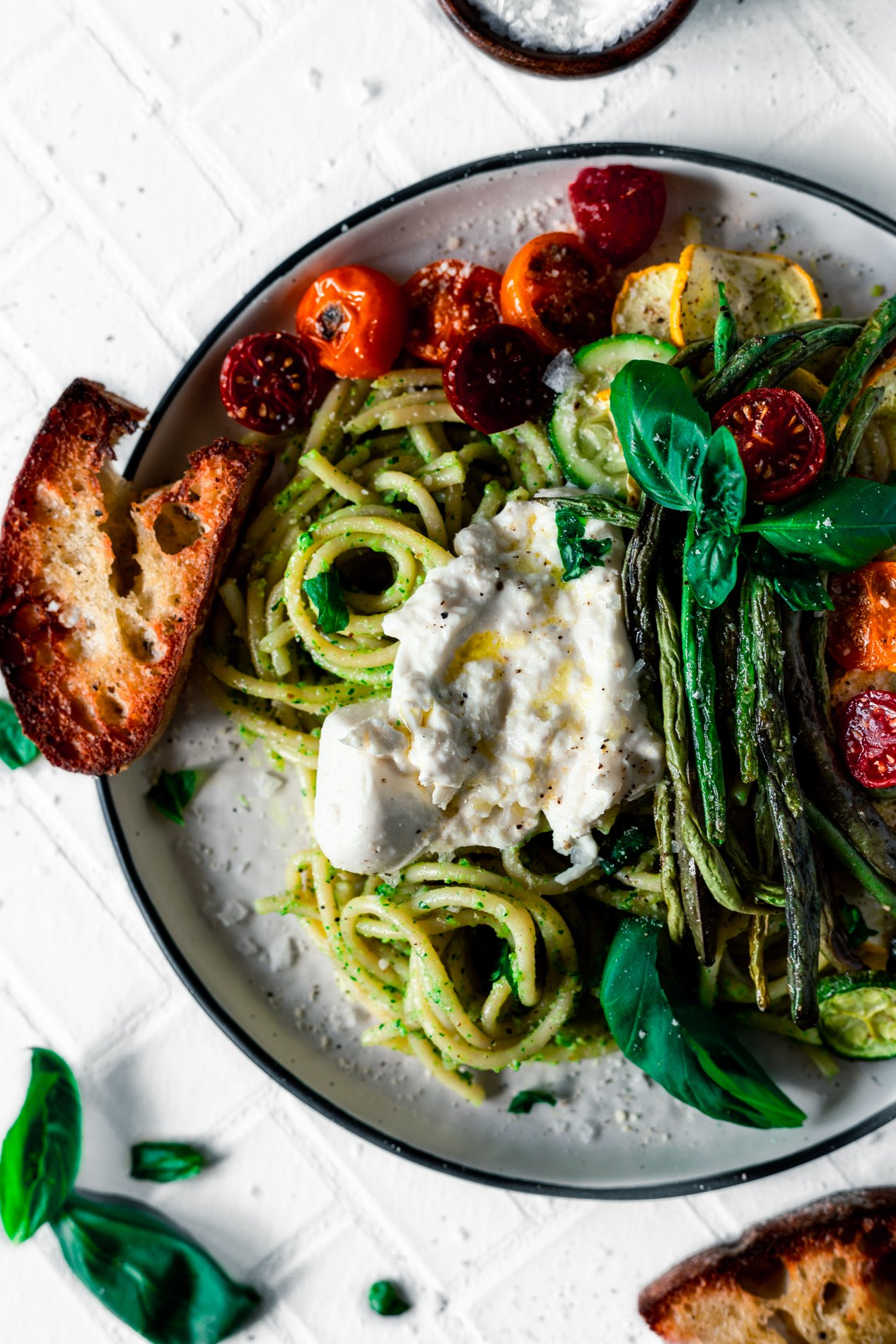 overhead closeup of a plate of walnut pesto pasta with roasted summer vegetables and a dollop of burrata