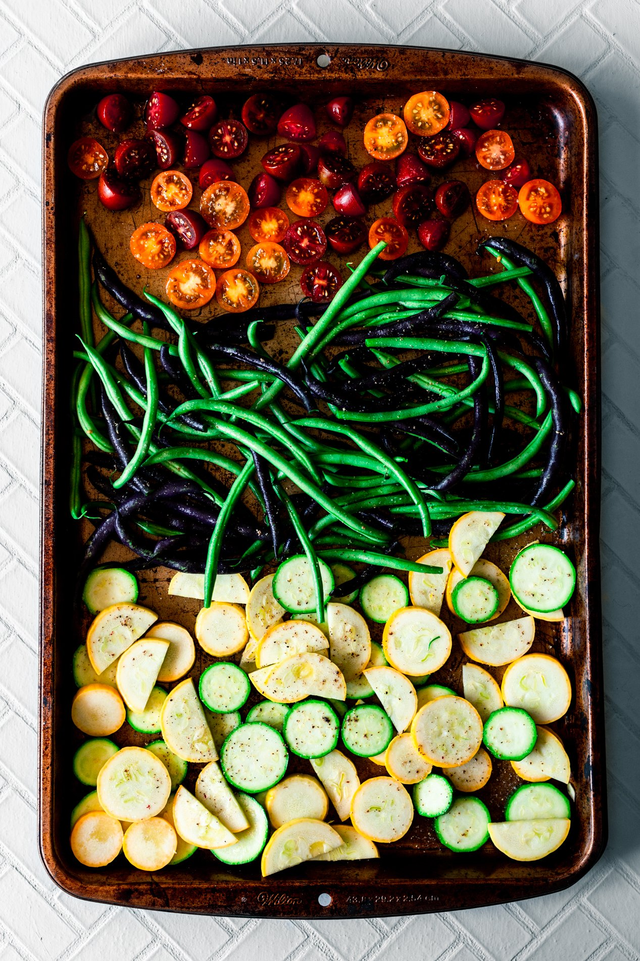 overhead view of a sheet pan full of cherry tomatoes, green and purple beans, and zucchini and squash ready for roasting