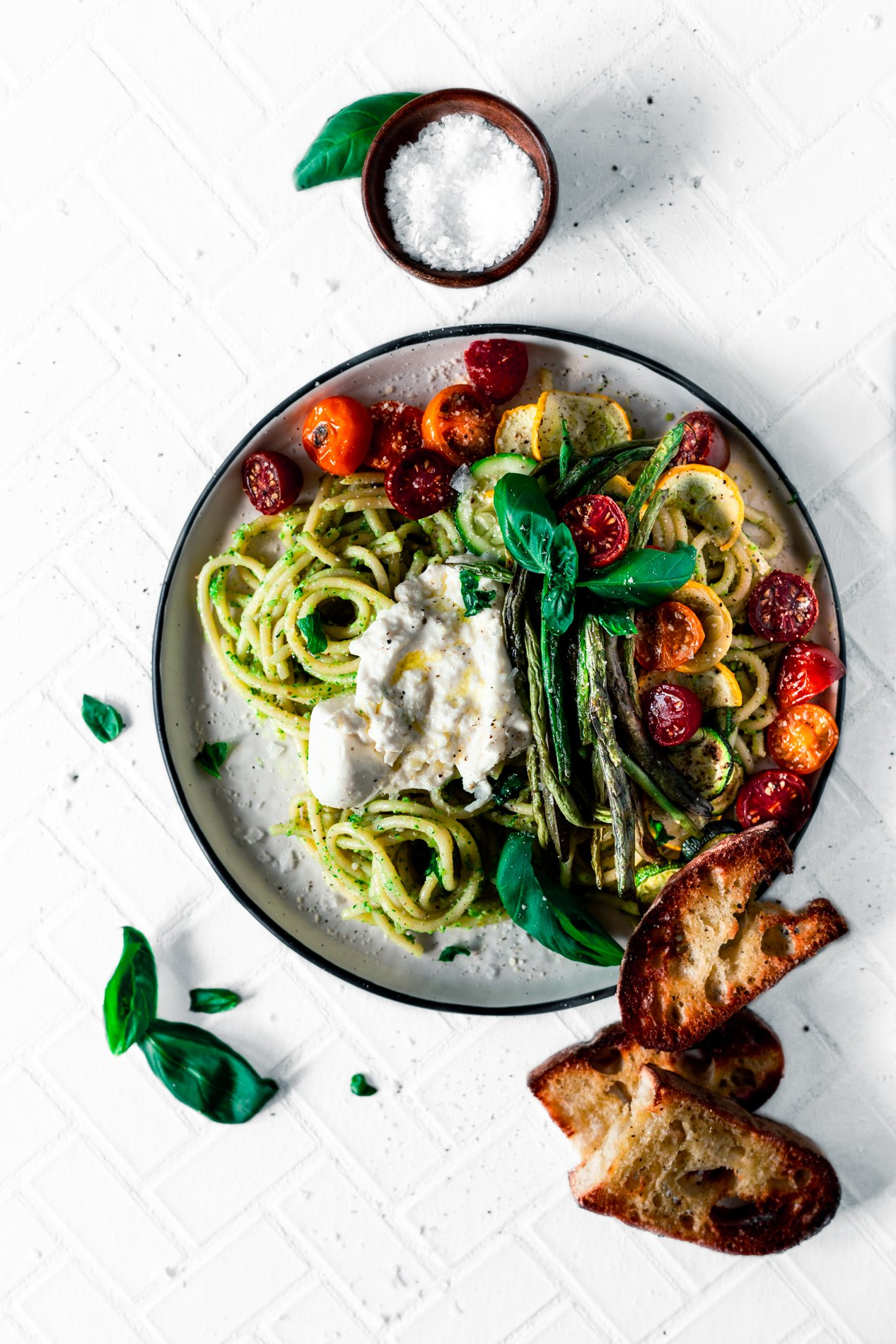 overhead view of a plate of walnut pesto pasta with roasted summer vegetables and a dollop of burrata with crusty toasted bread