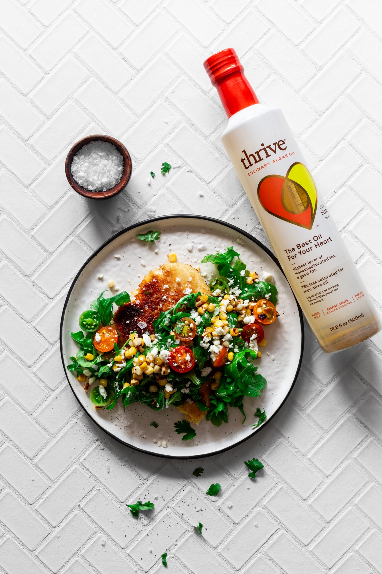 overhead view of a plate of easy chicken milanese recipe with charred corn, tomato, and arugula salad with a bottle of thrive culinary algae oil laying on its side