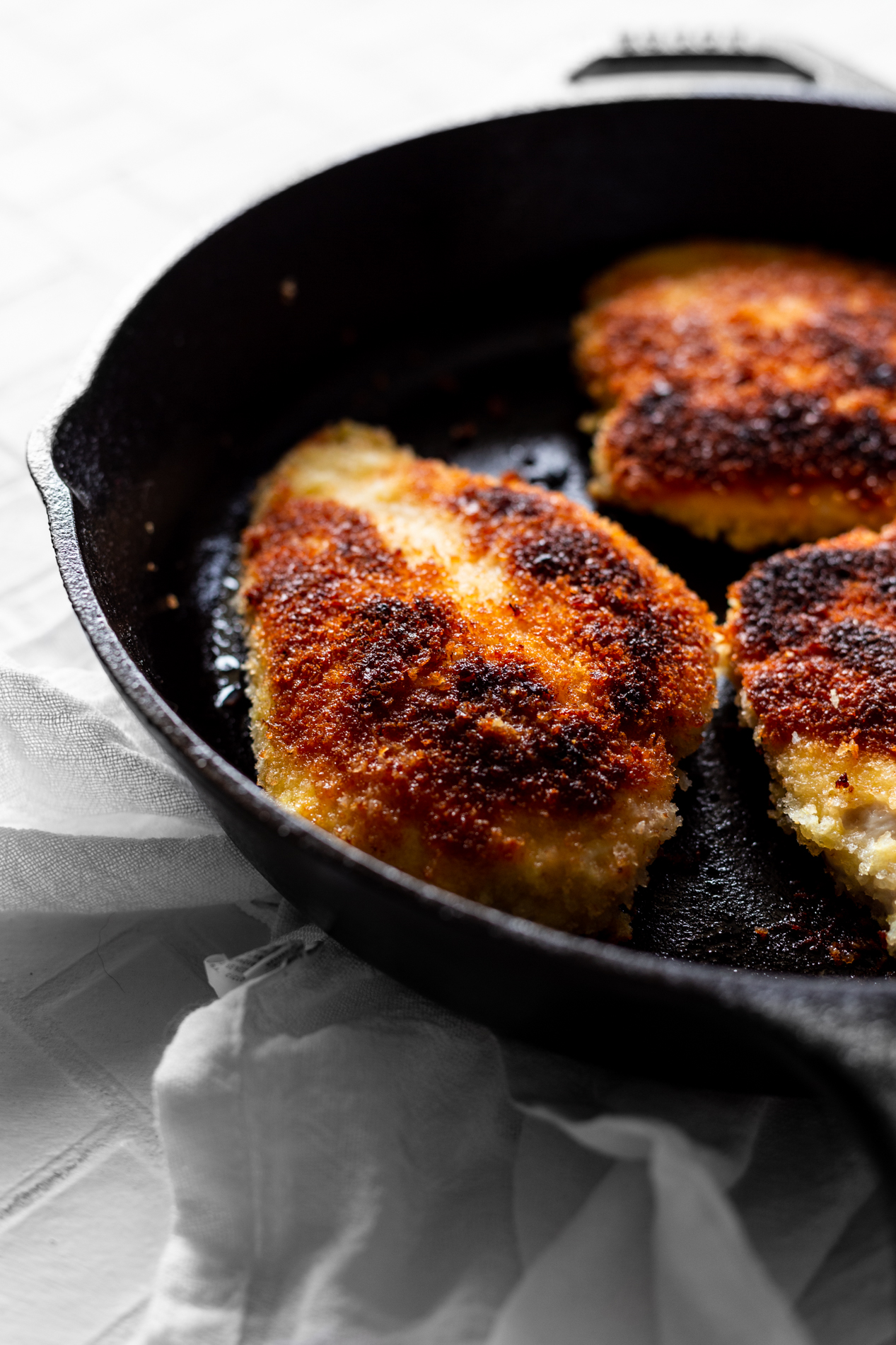 angled view of chicken milanese being cooked in a cast iron skillet
