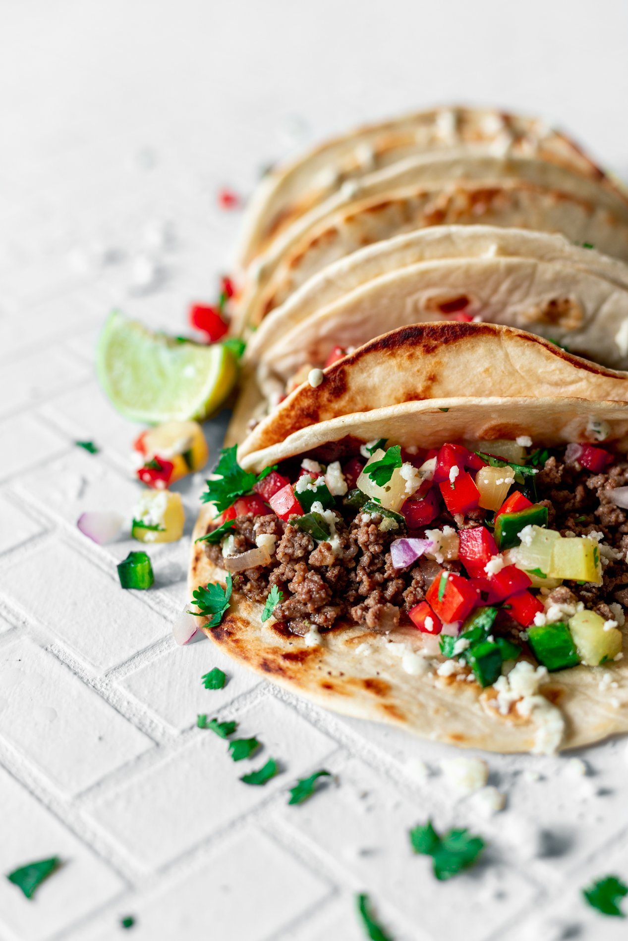 angled view of a row of pineapple beef tacos with poblano salsa