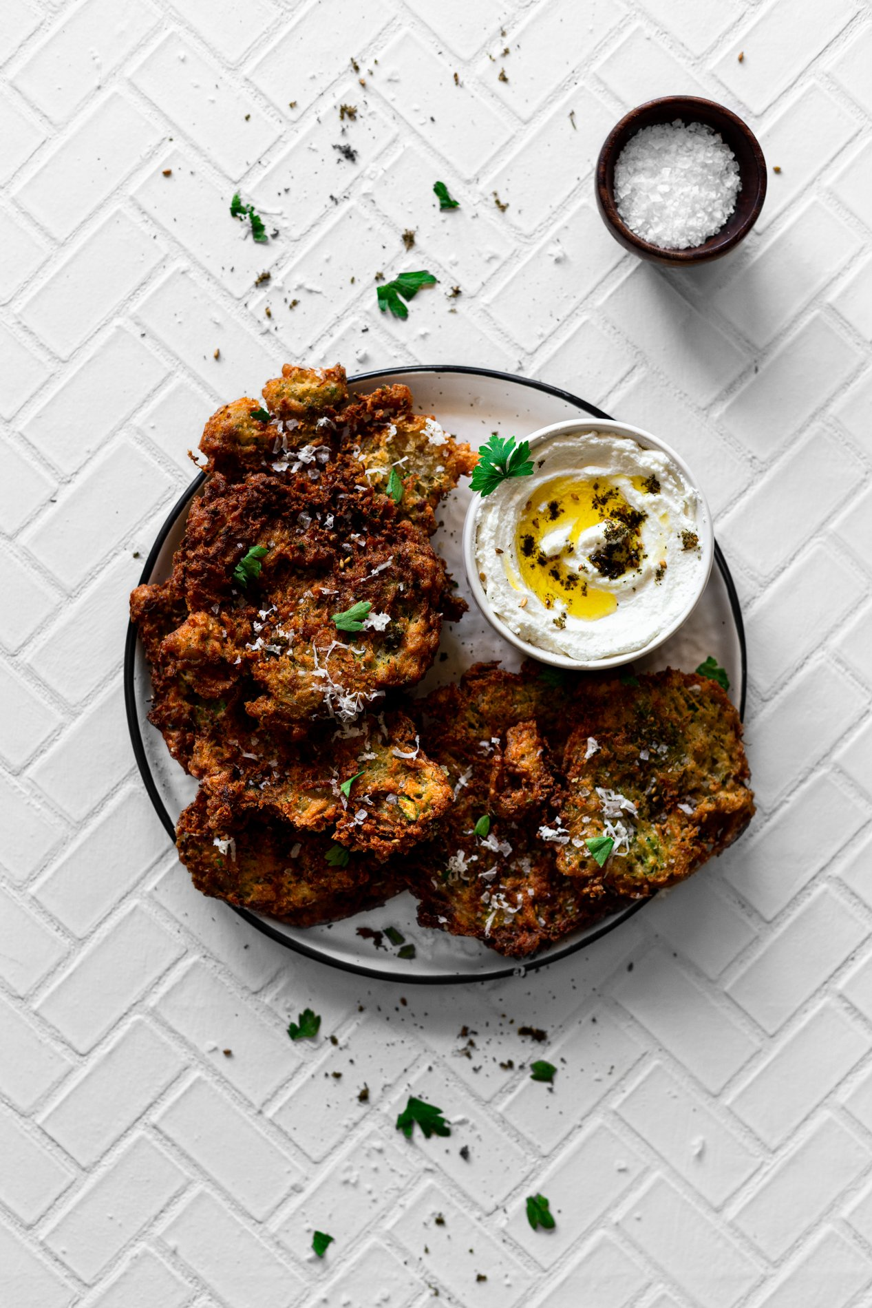 overhead view of za'atar spiced zucchini fritters with homemade labneh