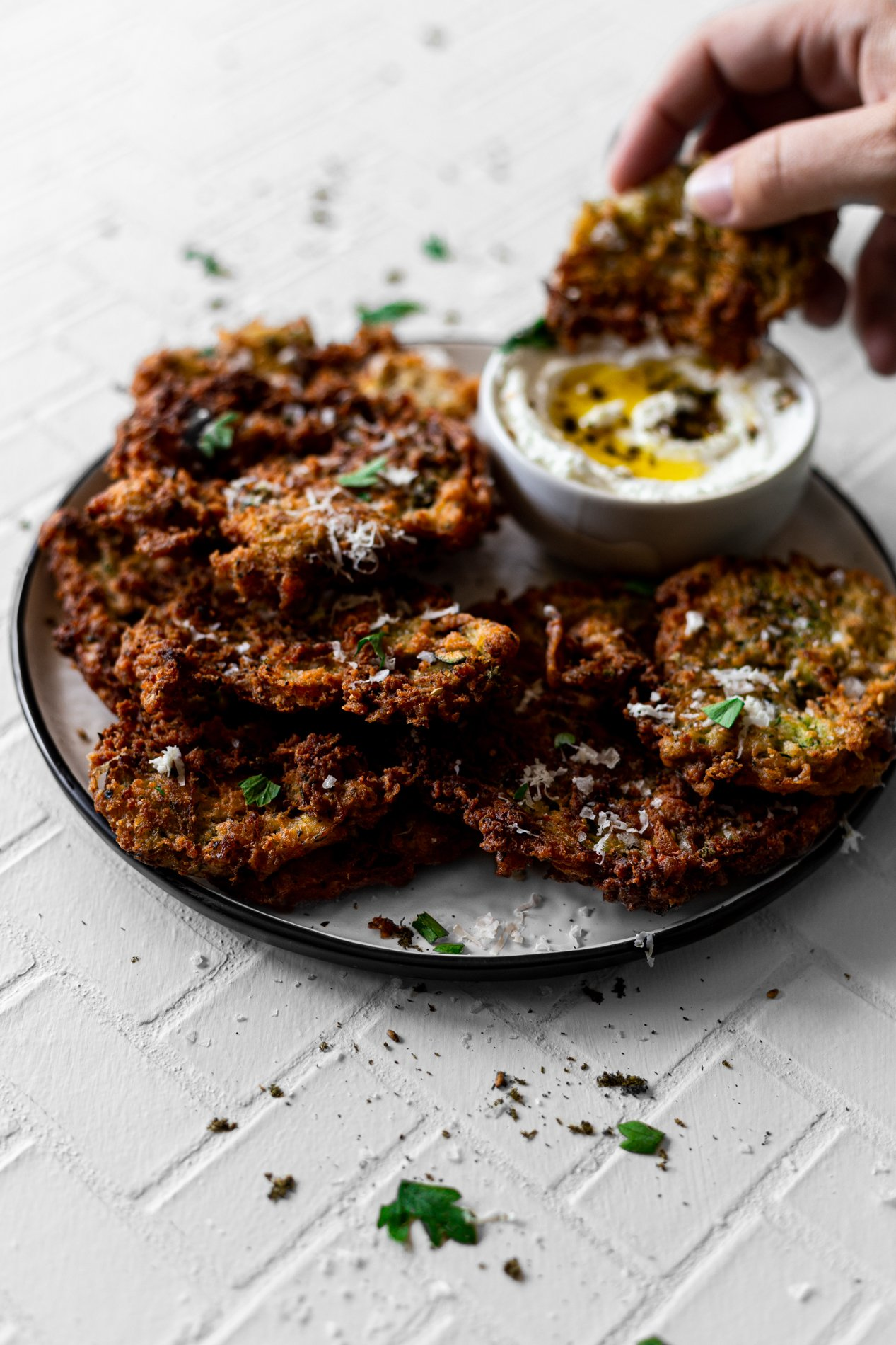 angled view of a plate of za'atar spiced zucchini fritters with one fritter being dipped into a bowl of homemade labneh