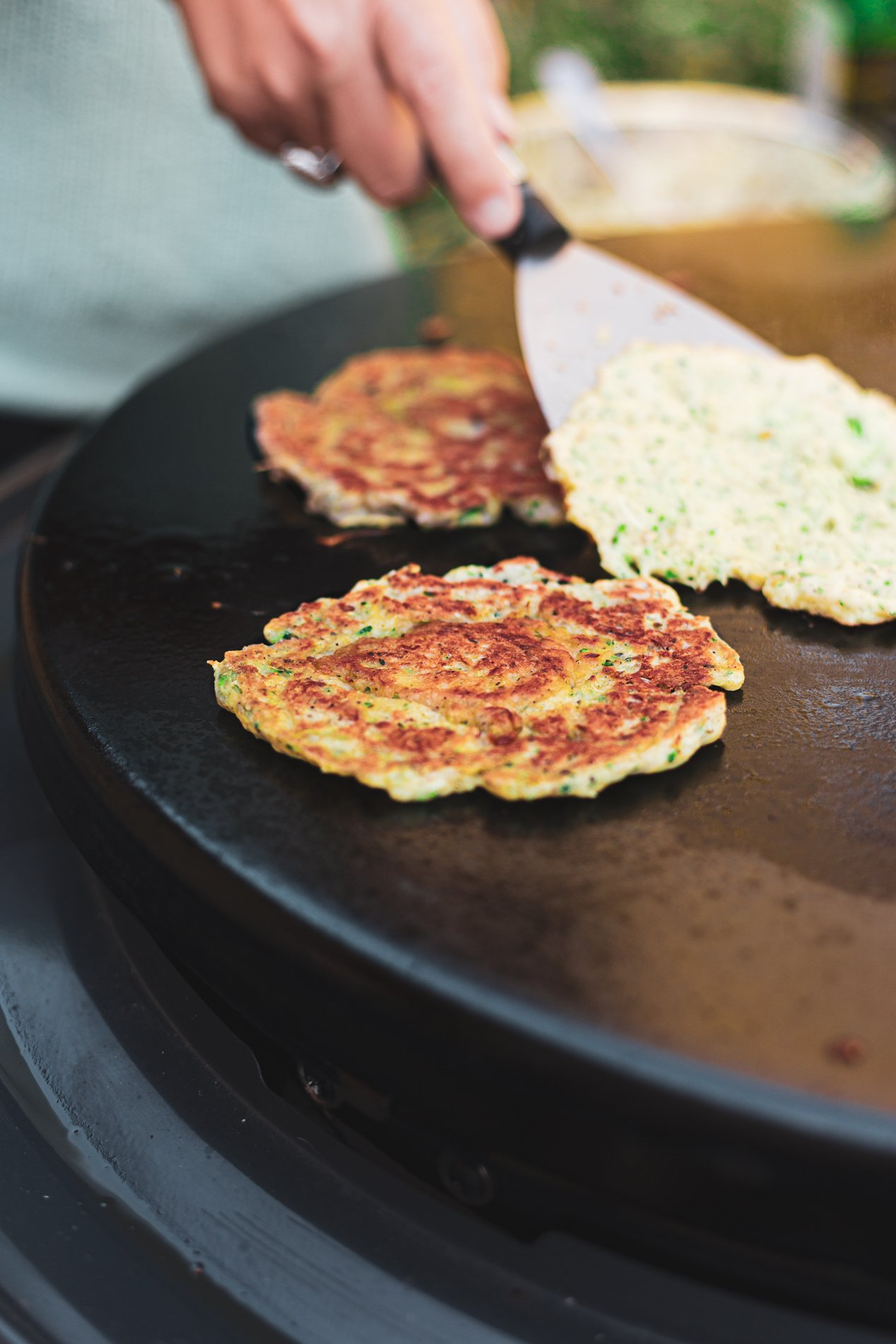 angled view of za'atar spiced zucchini fritters being cooked on the Cuisinart 360 Degree Griddle Cooking Center