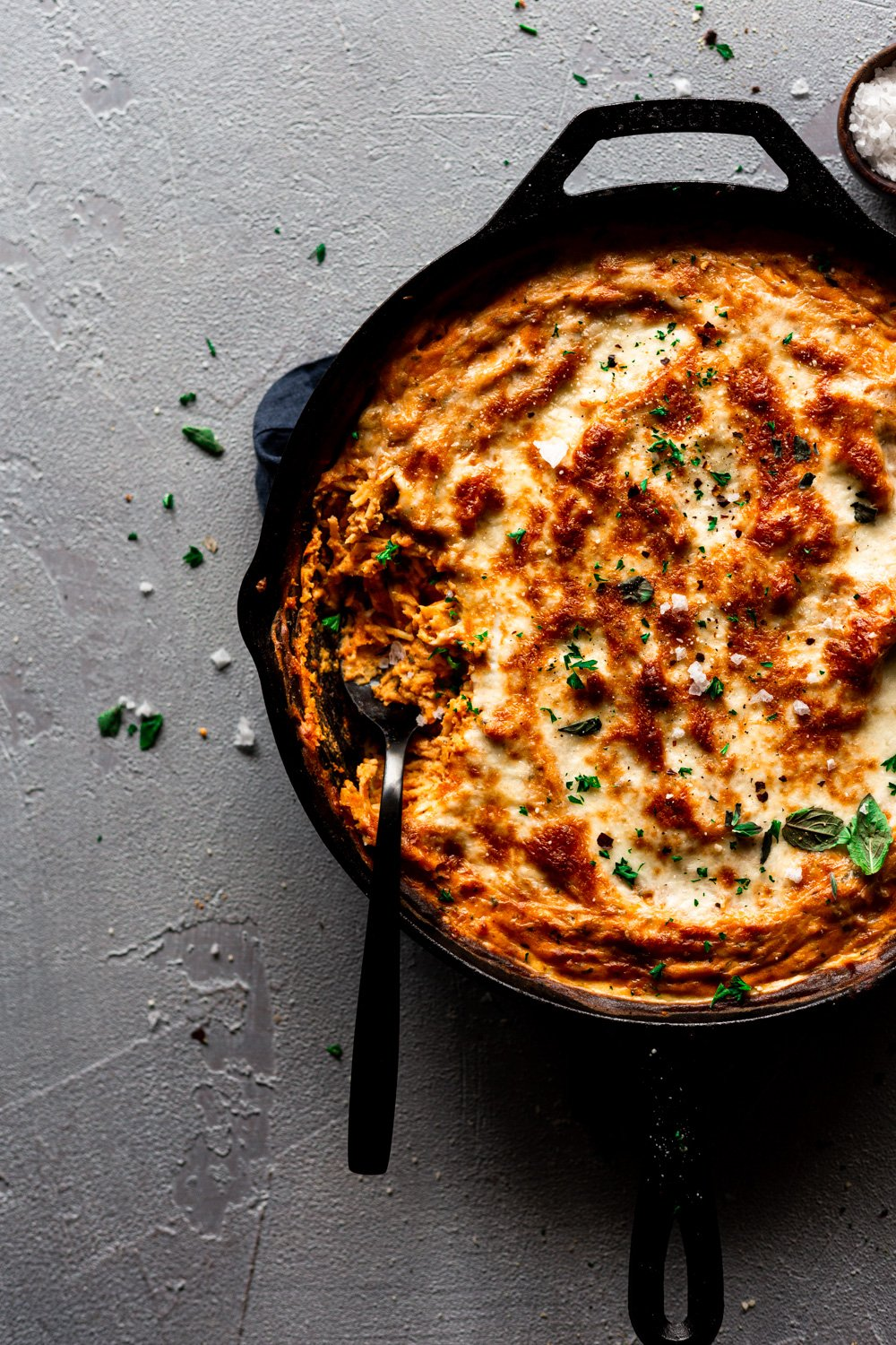 gluten free spaghetti pie in a cast iron skillet with a serving spoon