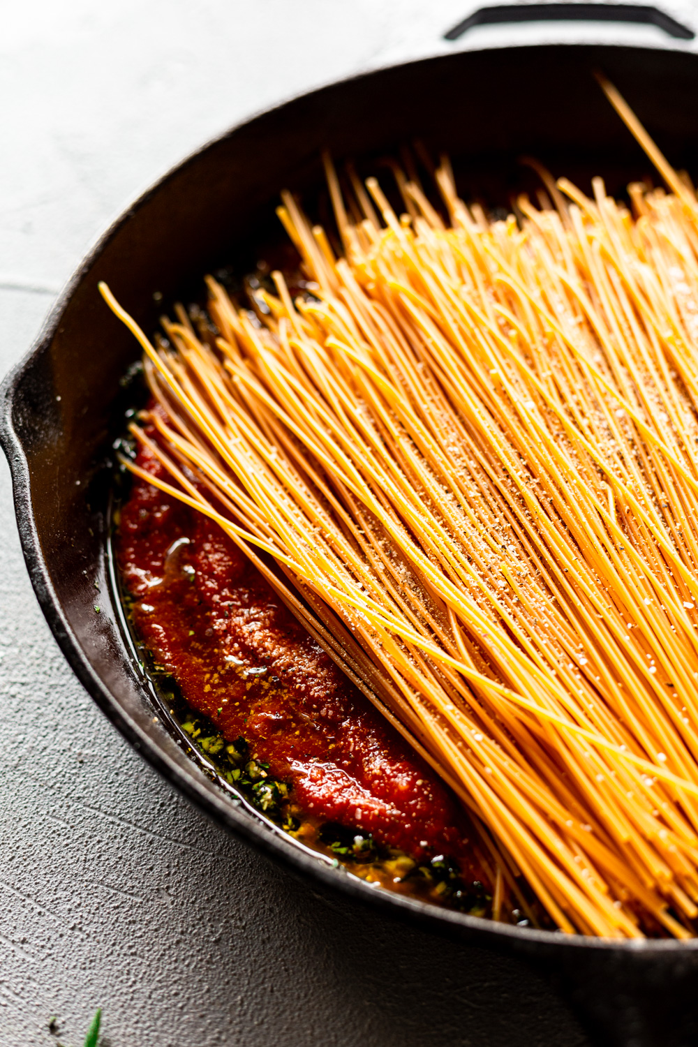 gluten free pasta added to a cast iron skillet with herbs and sauce