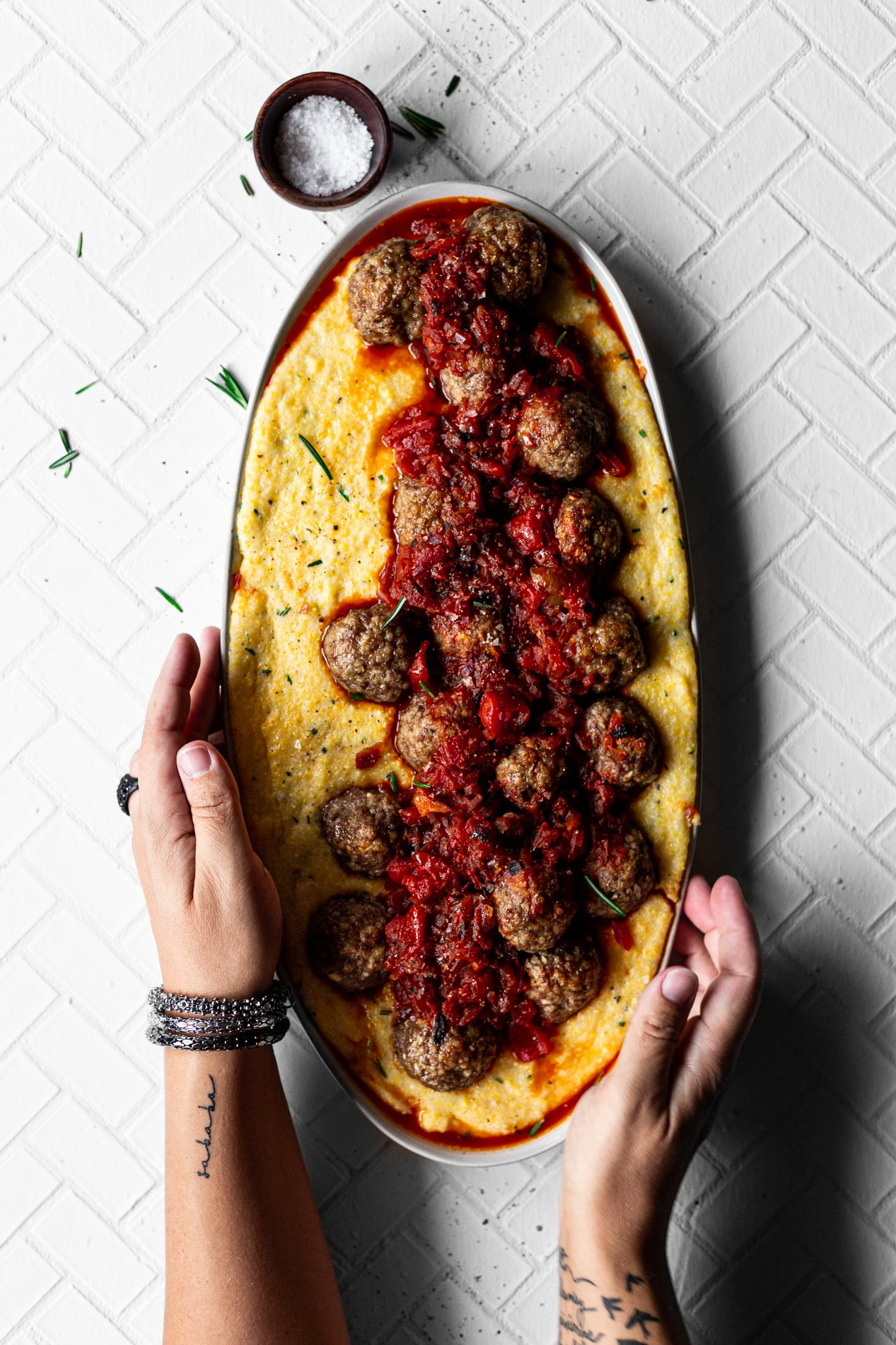platter filled with honeyed-rosemary polenta topped with lamb meatballs and red pepper sauce