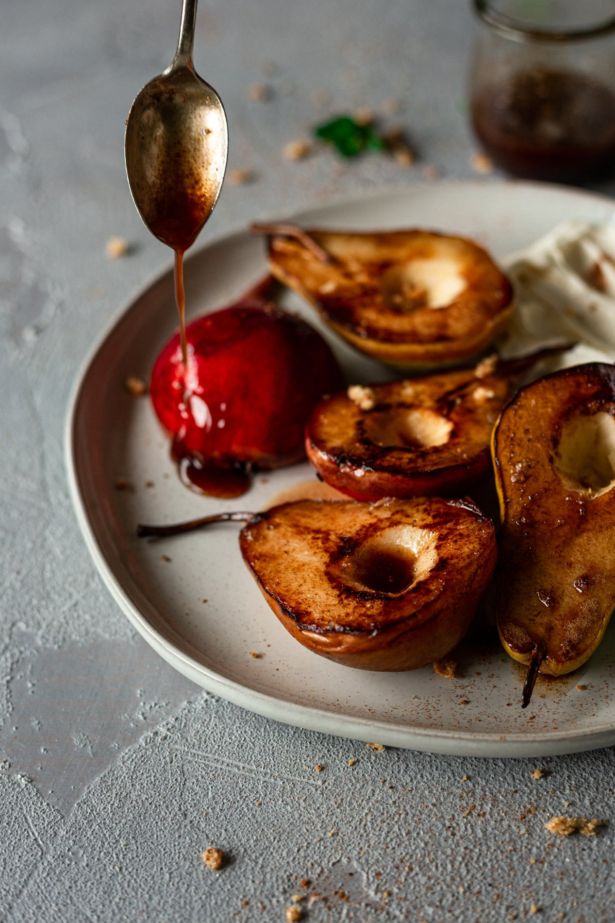 angled view of roasted pears with honey-spiced browned butter being drizzled on them