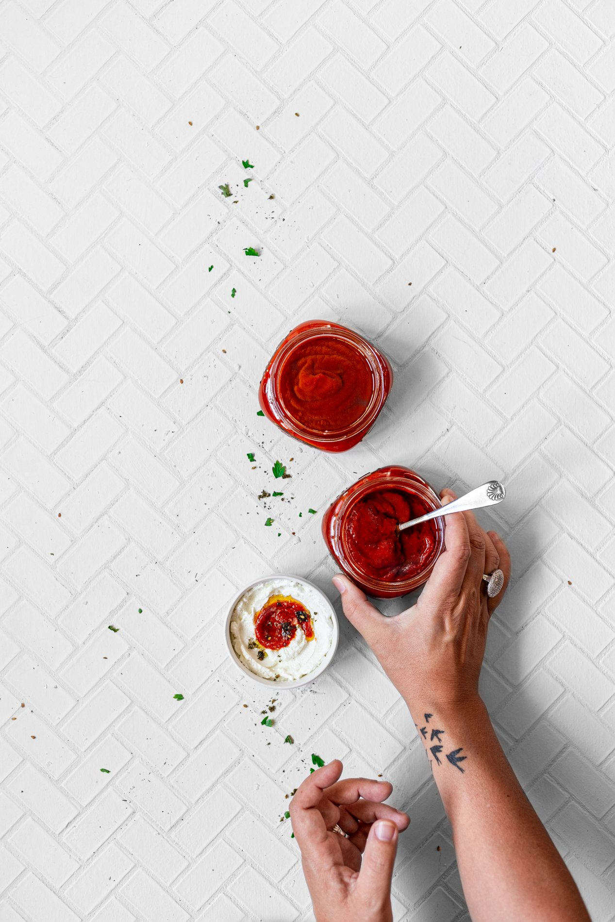 overhead view of two jars of roasted red bell pepper paste and a small bowl of labneh