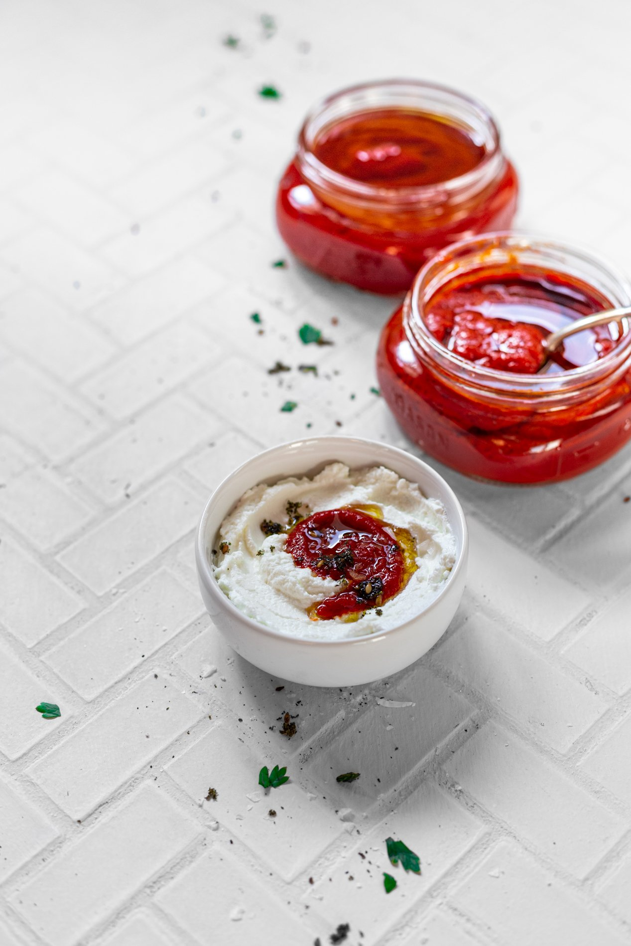 two jars of roasted red bell pepper paste and a small bowl of labneh topped with a dollop of paste
