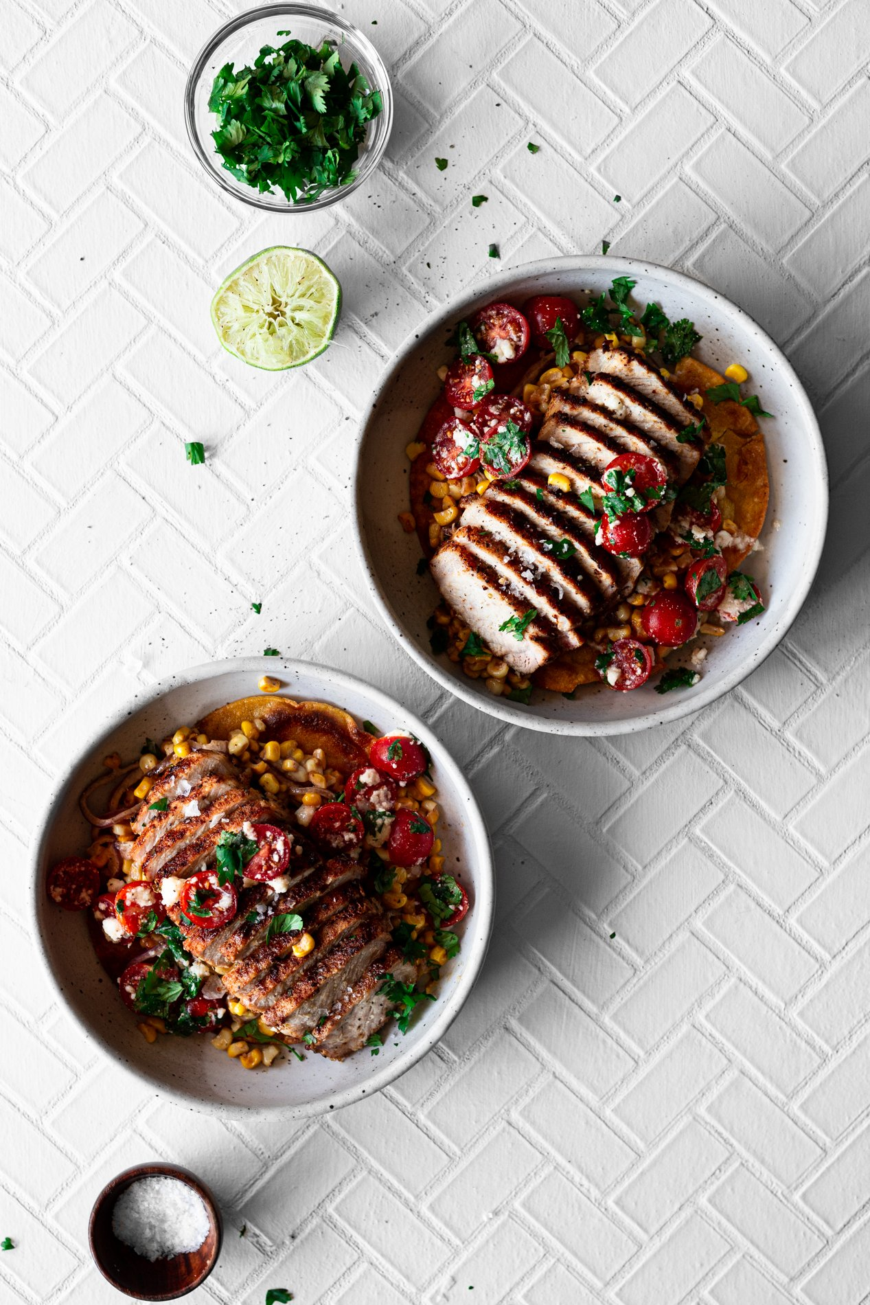 two bowls of spiced fajita pork on mexican street corn with fresh salsa