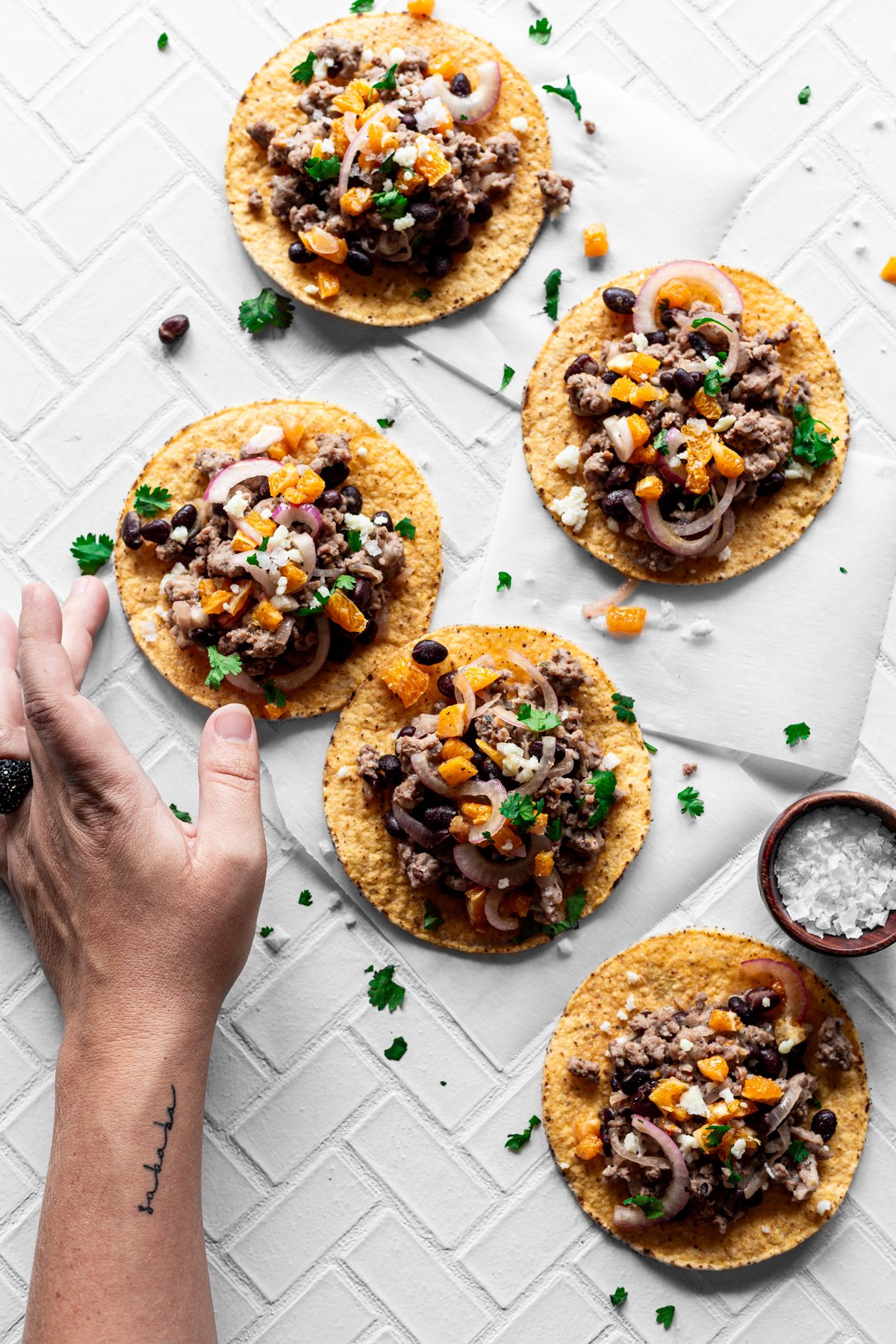 Five mojo pork tostadas with orange salsa, queso fresco, and cilantro
