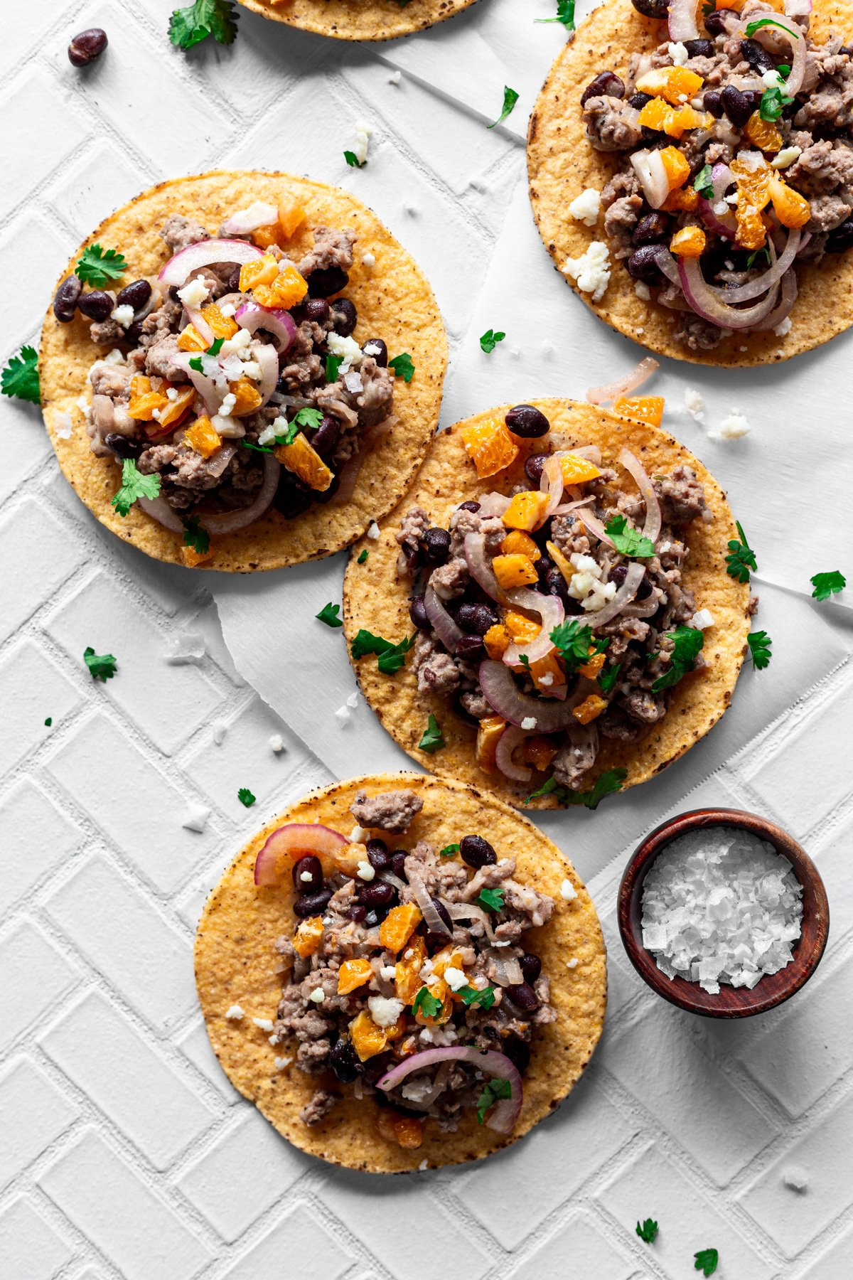 four mojo pork tostadas with queso fresco, orange salsa, and cilantro