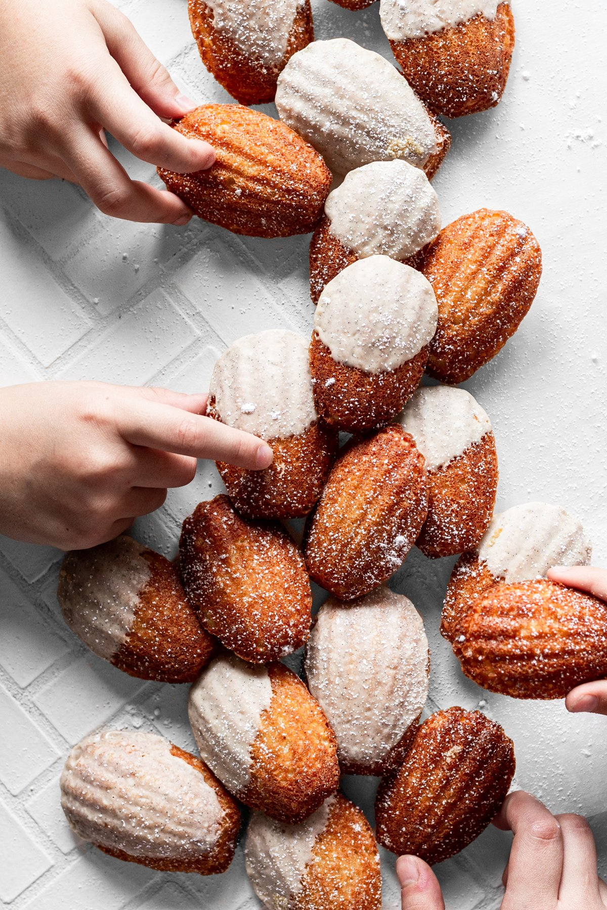 four hands grabbing vanilla bean browned butter madeleines