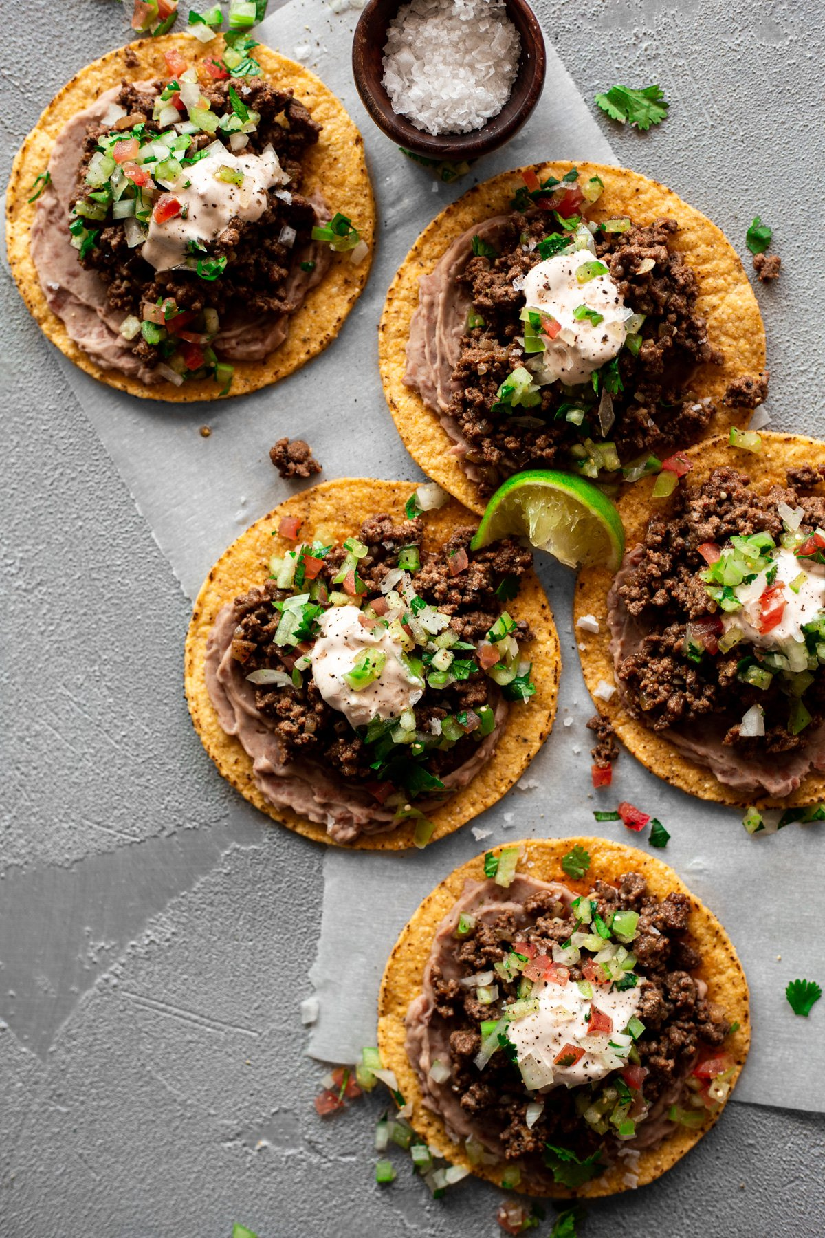 five bean and beef tostadas with tomatillo salsa and chipotle crema and lime