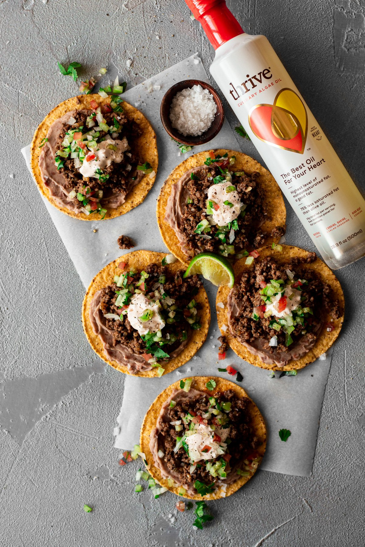 a bottle of Thrive Algae Oil beside five bean and beef tostadas