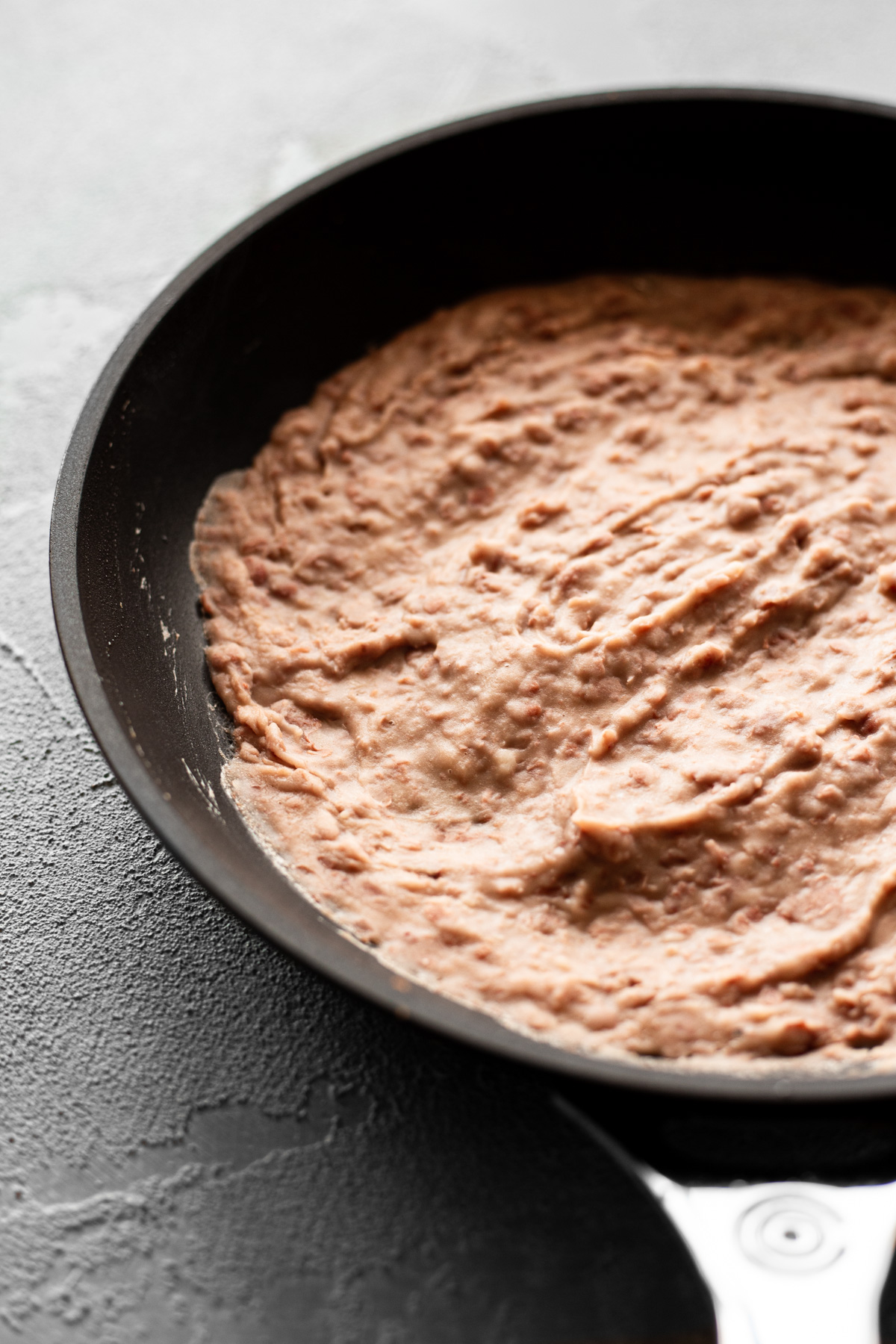 skillet filled with freshly mashed pinto beans for bean and beef tostadas