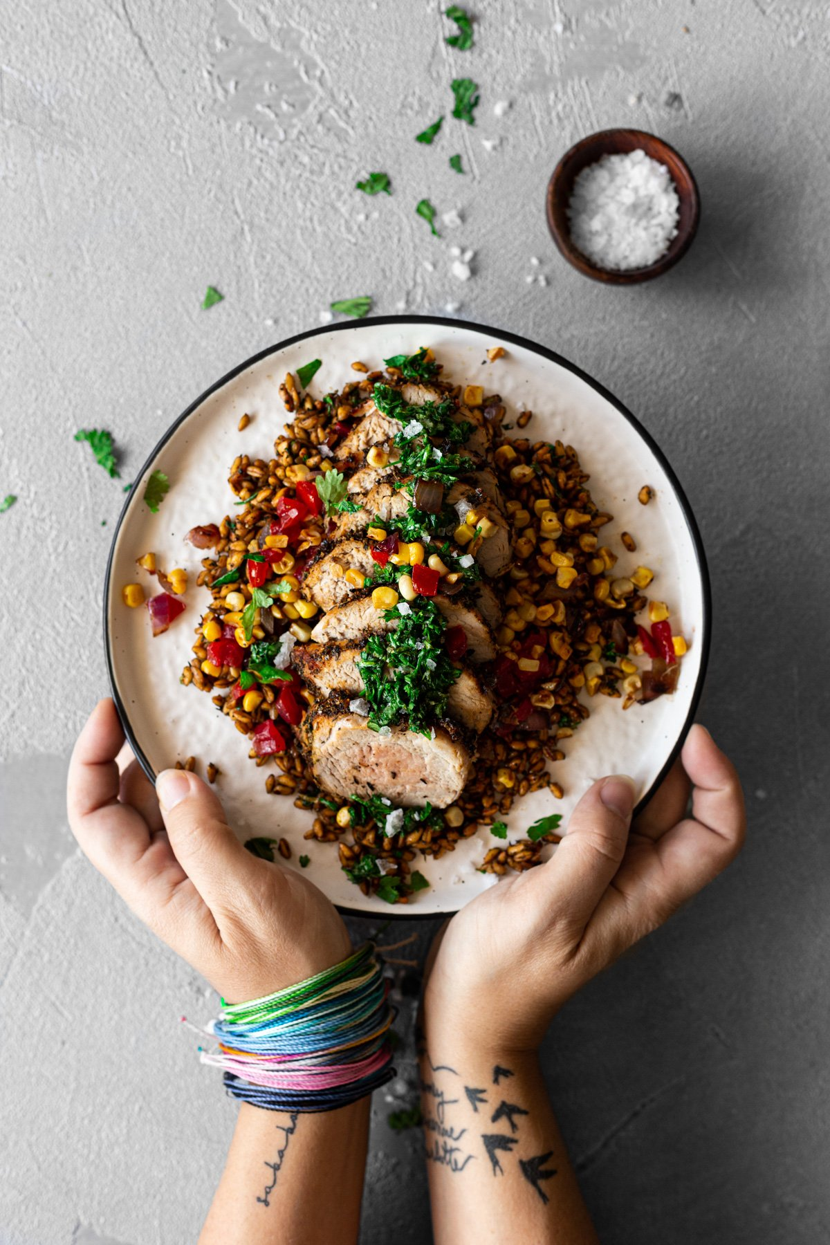 hands holding a plate with chimichurri air fryer pork tenderloin with farro salad